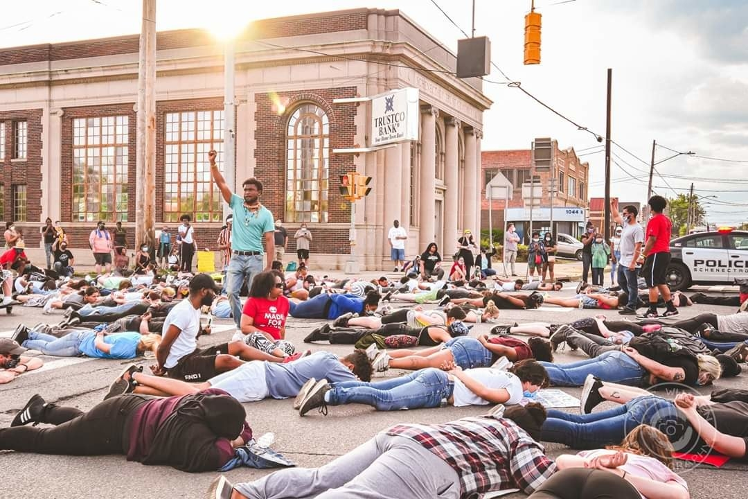 One man stands in the middle of the street with his arm raised while people lay face-down with their arms behind their backs on the ground all around him