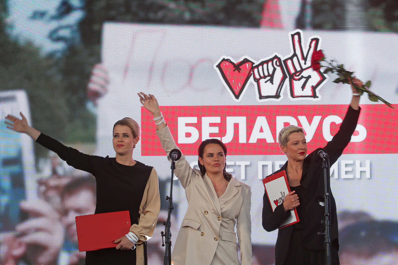 "Three women stand on a stage with the arms raised, waving to the crowd. Behind them are their campaign symbols: a heart, a fist, and a hand making a ""V"" for victory"