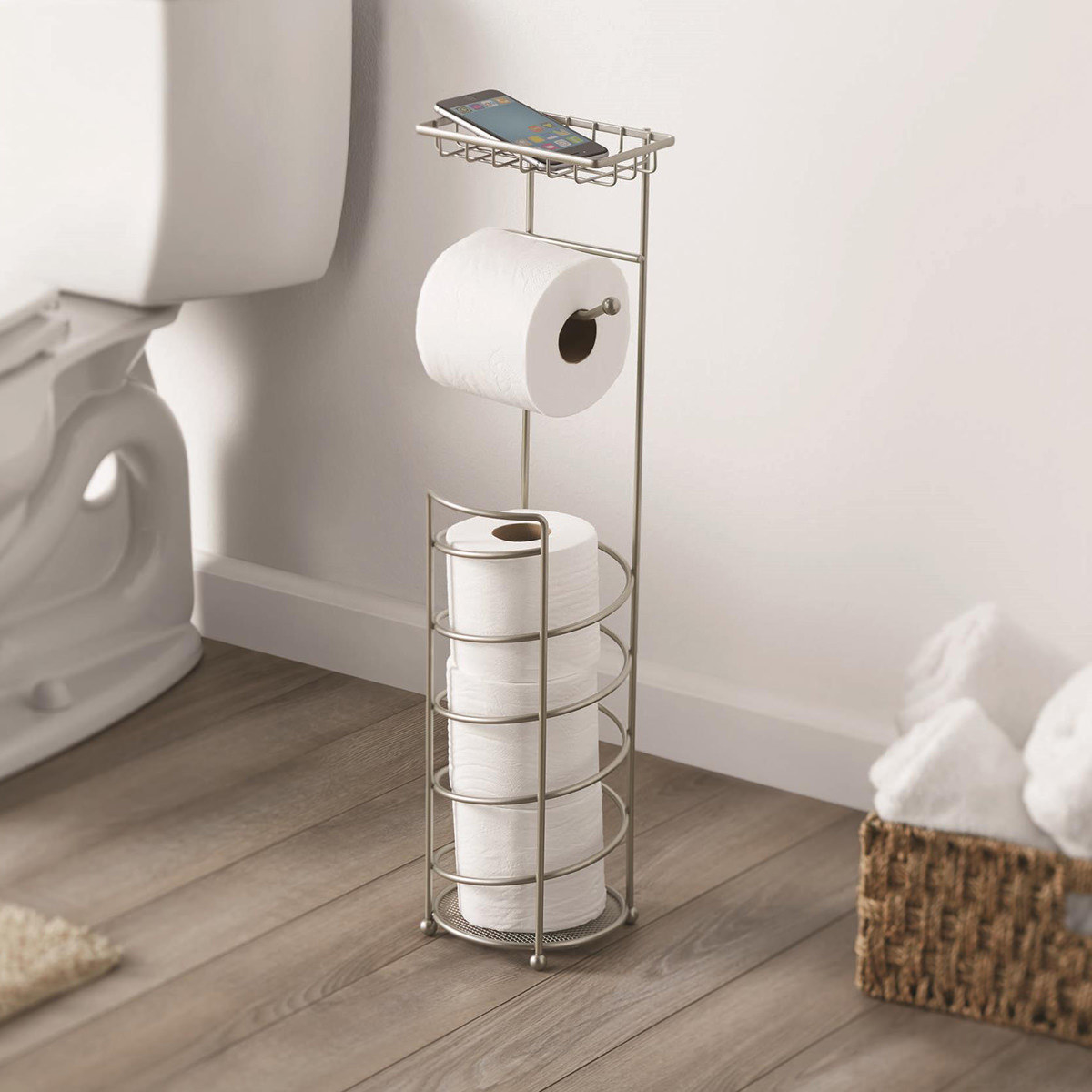 The metal toilet paper holder with a bottom section for rolls, a rod for the roll in use, and phone shelf on top