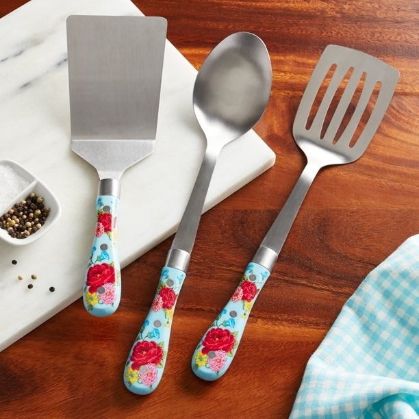 Three silver cooking utensils with baby blue, floral-accented handles