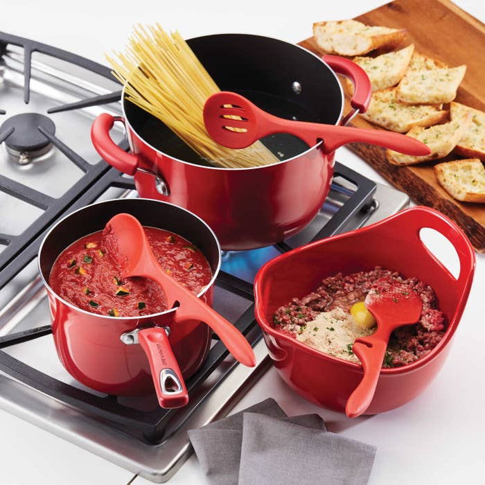 Red pans on a stove with red silicone spoons propper on the edge