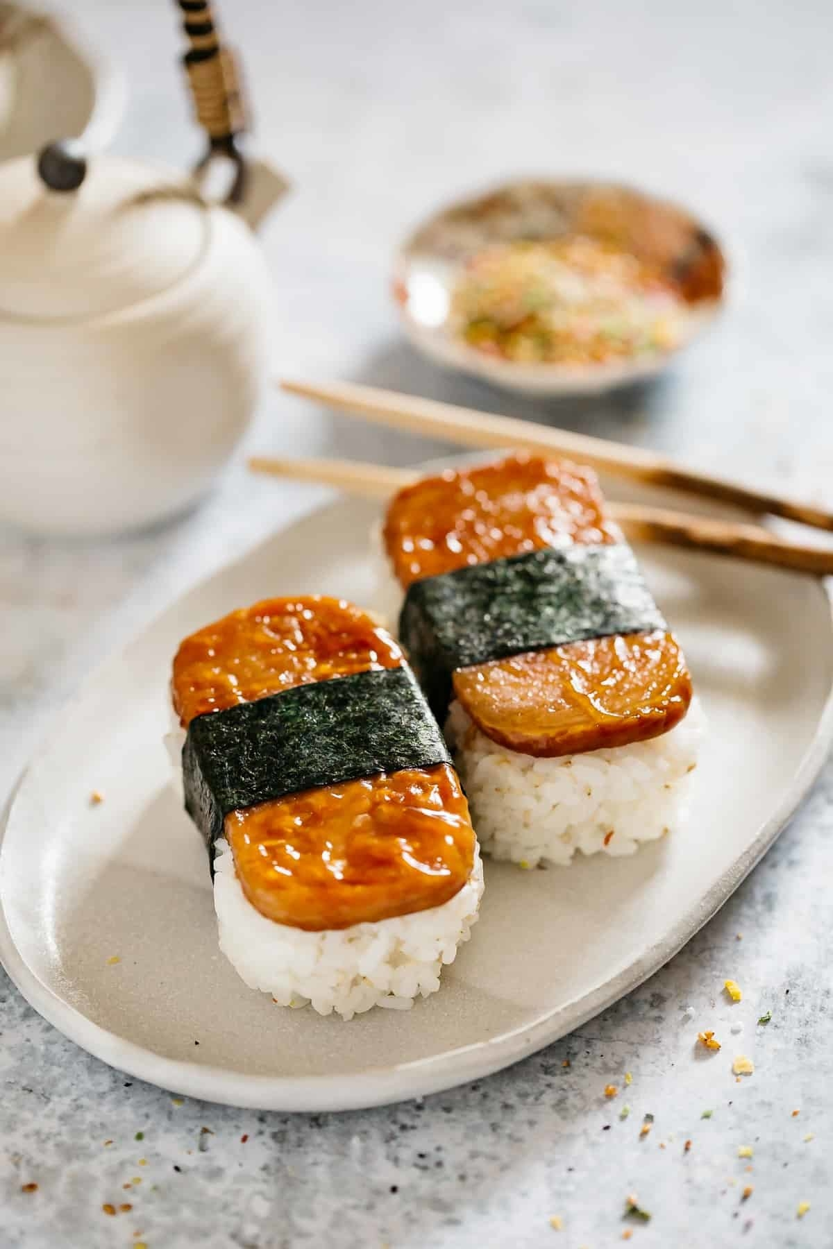 Two slices of spam sit atop thick piles of rice and are tied together with a strip of crisp seaweed.