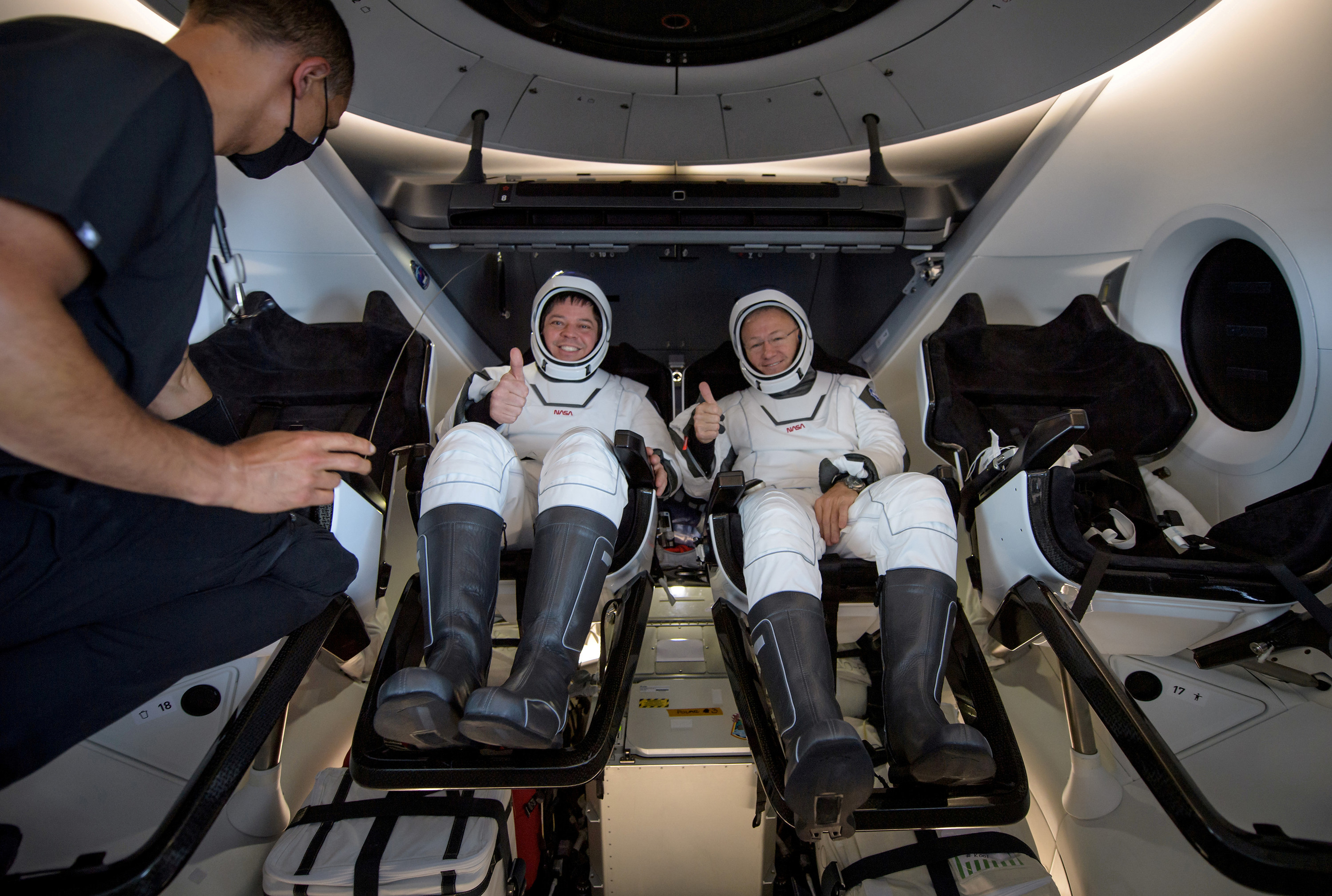 Two astronauts smile and give a thumbs-up as a man enters the capsule