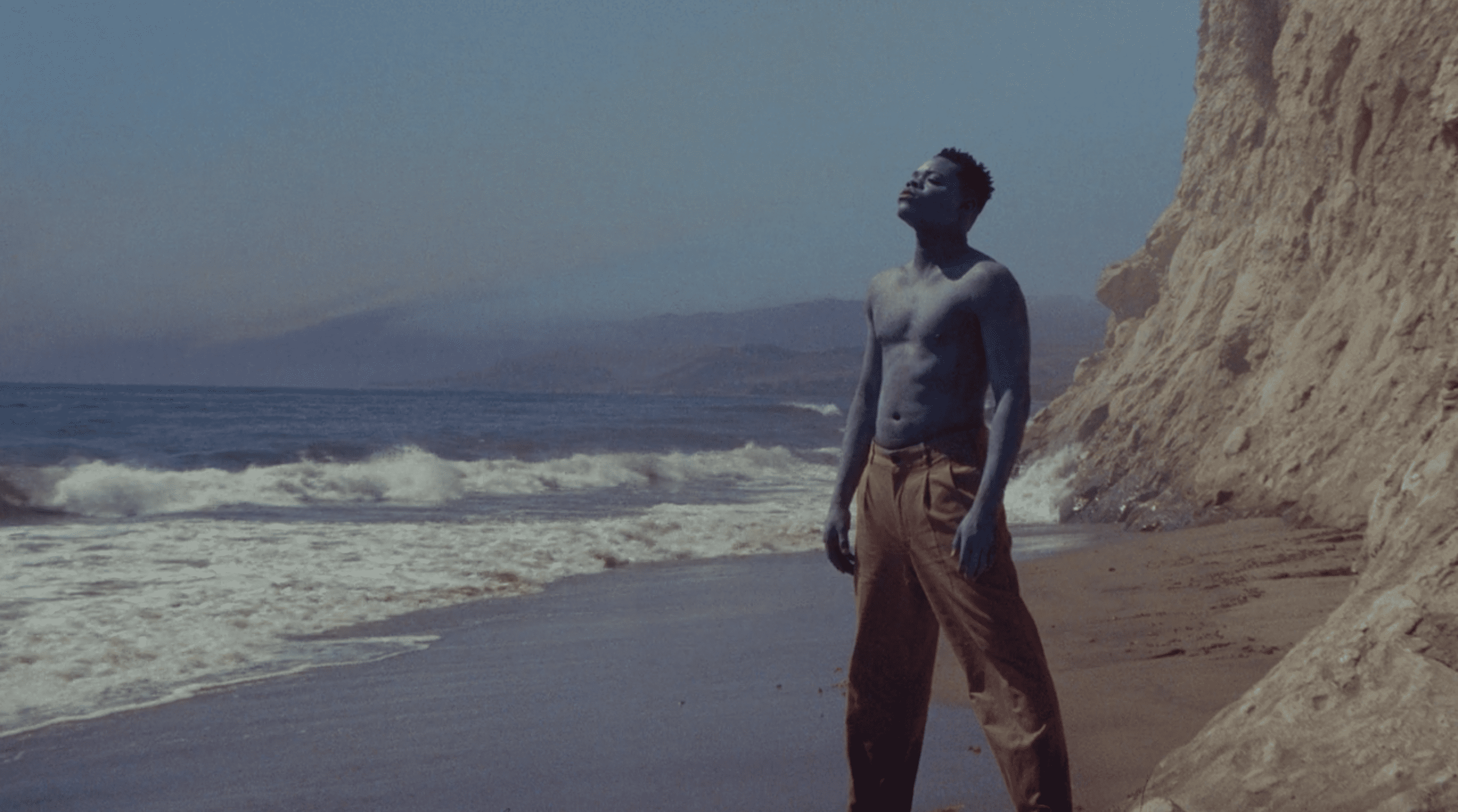 "Papi Ojo looks up at the sky as the blue man in ""Black Is King"""