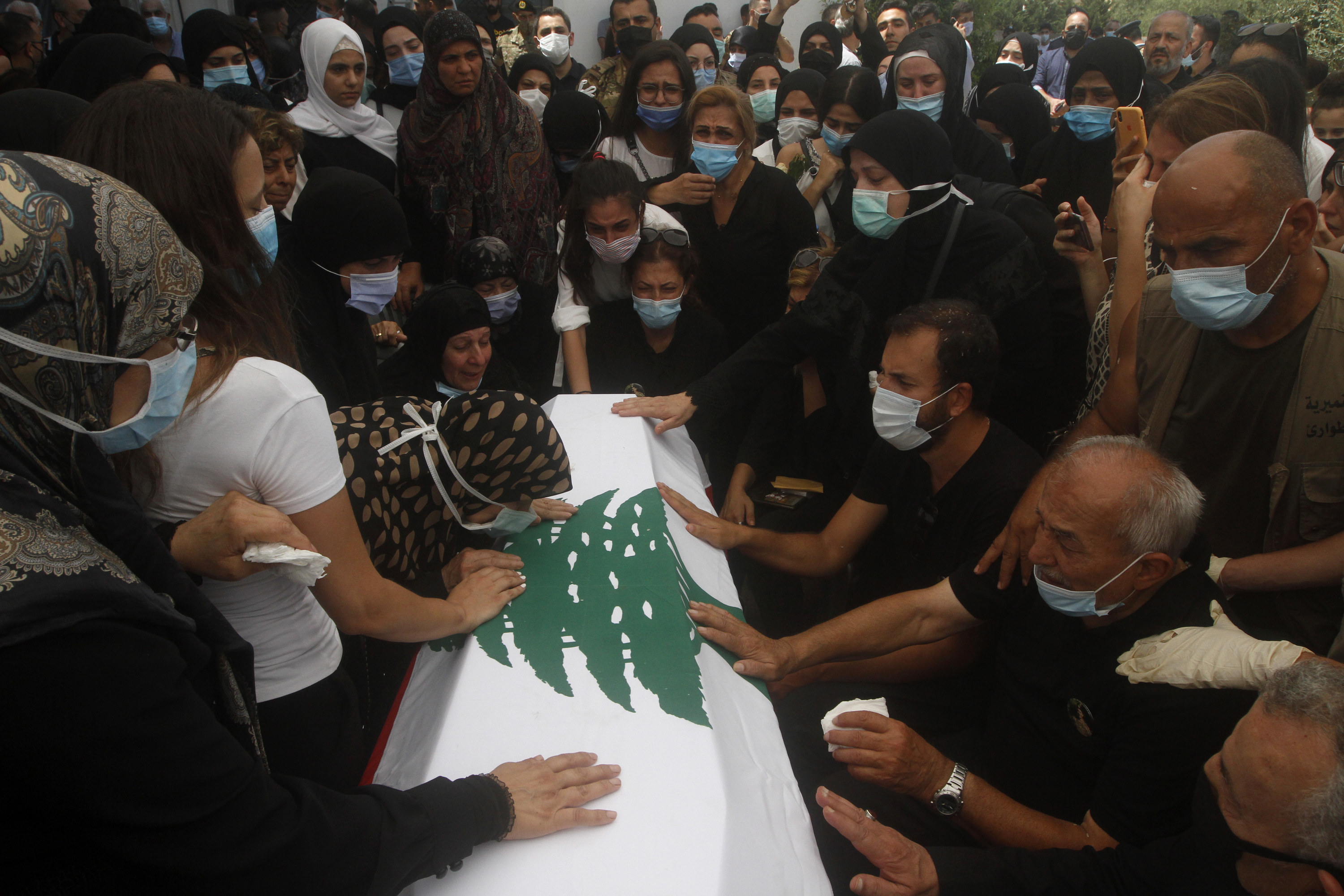 A crowd of people in black wearing masks touch a coffin covered in the Lebanese flag