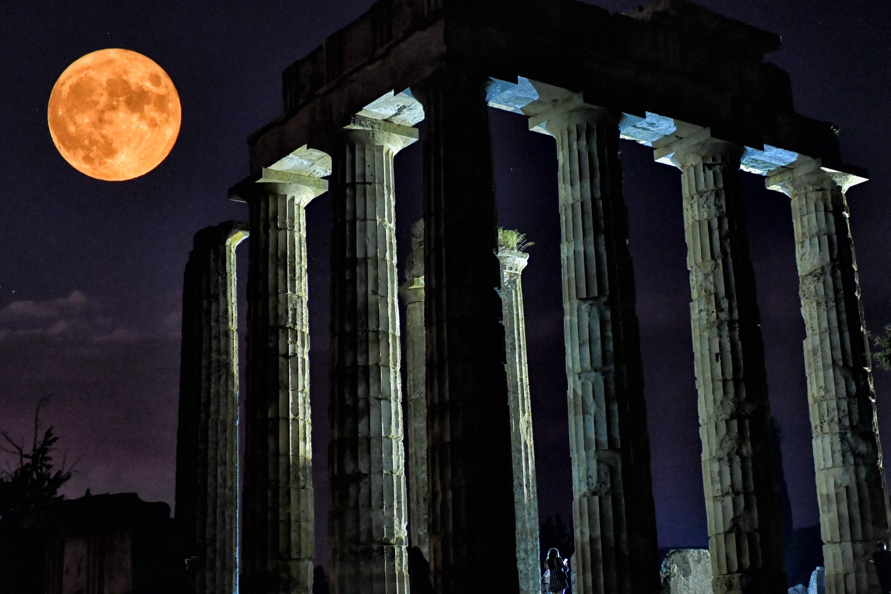 A full orange moon rises over the ruins of a colossal temple with gigantic columns
