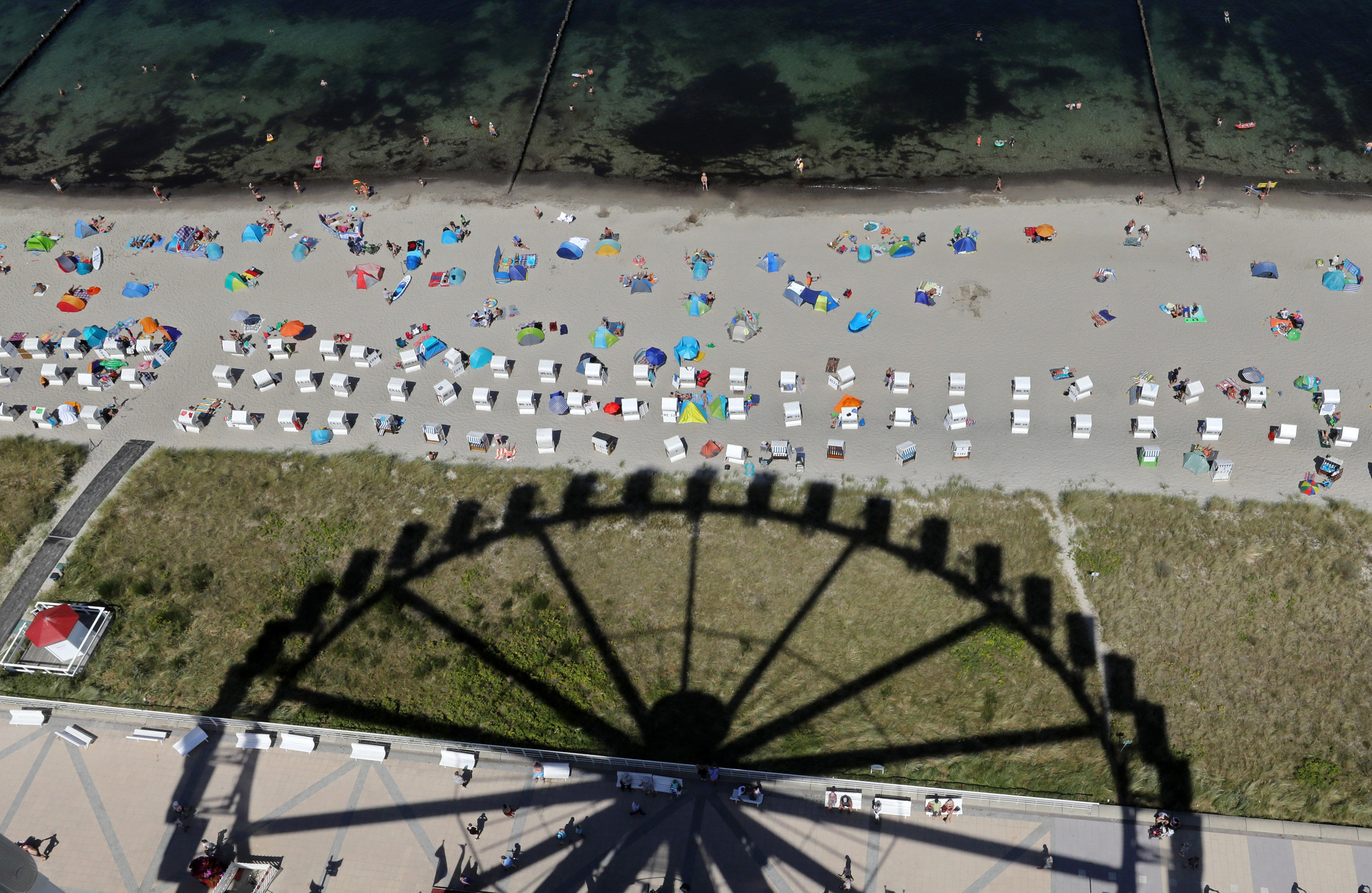 The shadow of a giant Ferris wheel looms over beachgoers with uniformly distanced cabanas and tents