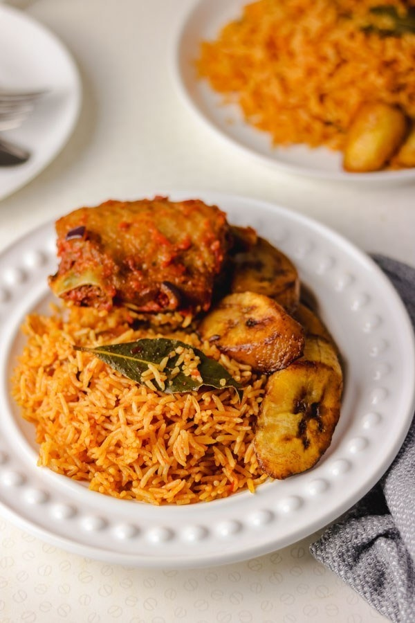 A shallow bowl holds orange-tinged rice, caramelized plantains, a bay leaf, and a piece of skin-on chicken with a thick red sauce