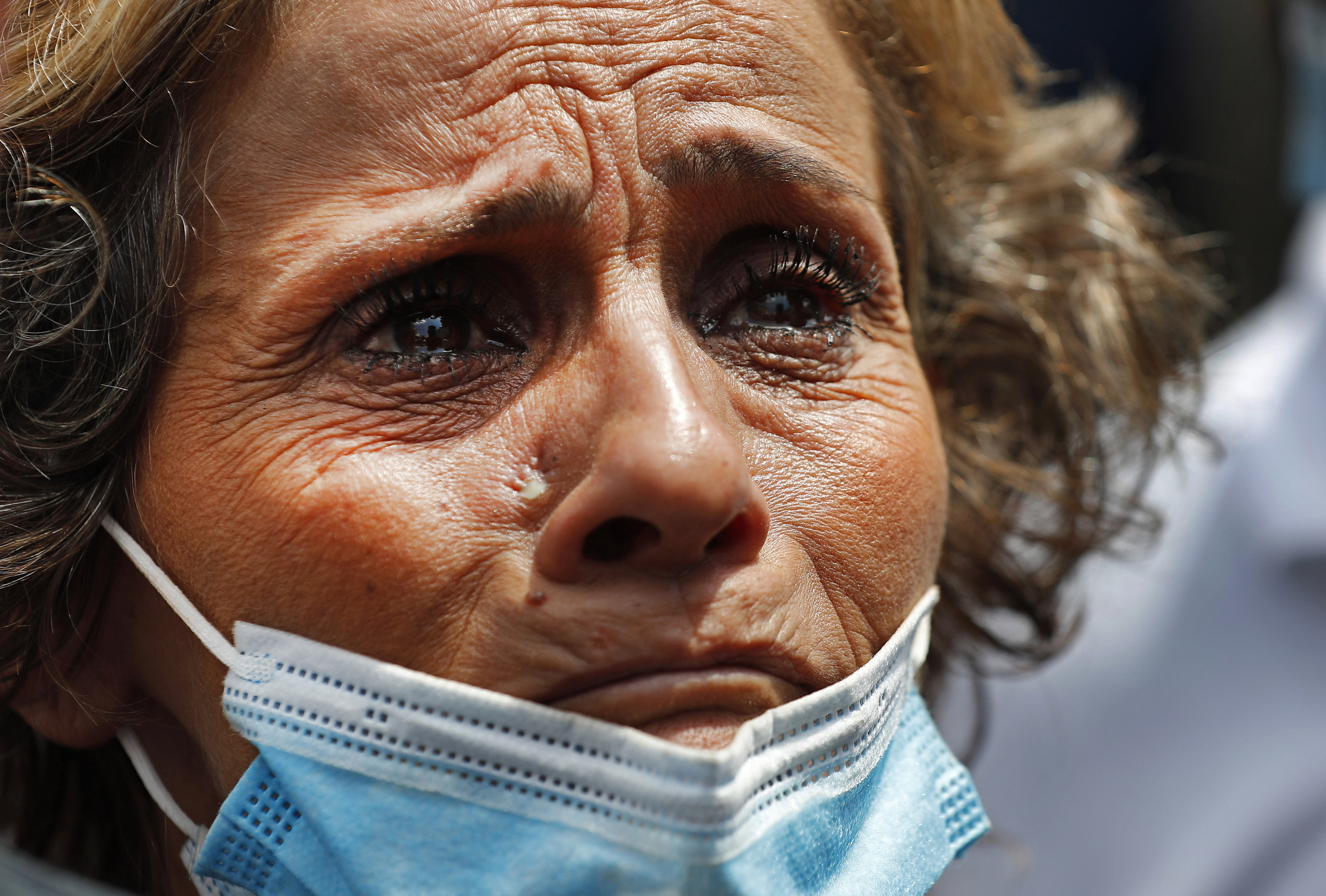 A crying woman wears a disposable blue mask pulled down to her chin
