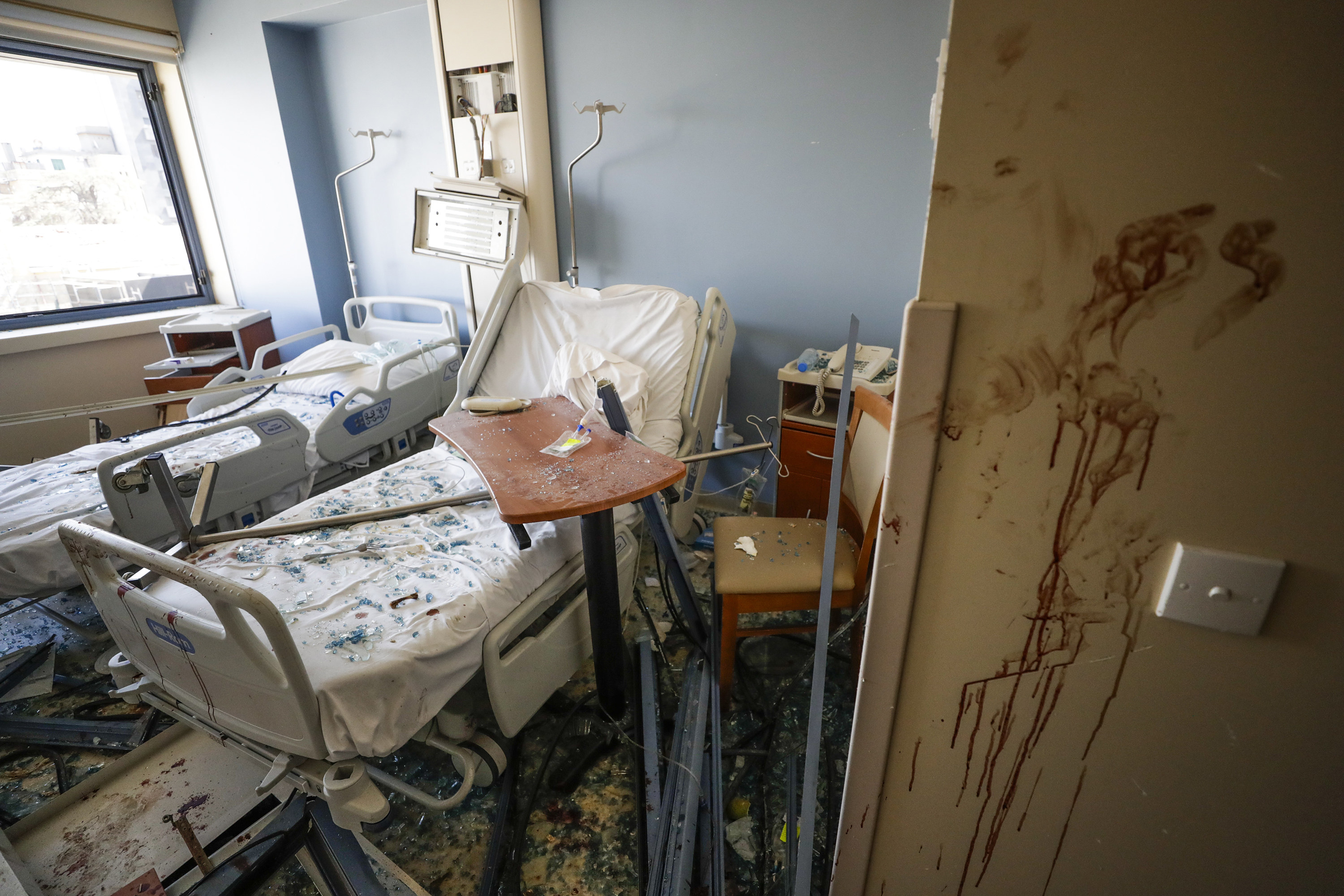A hospital room with two empty beds is seen covered in broken glass with blood splattered on the wall