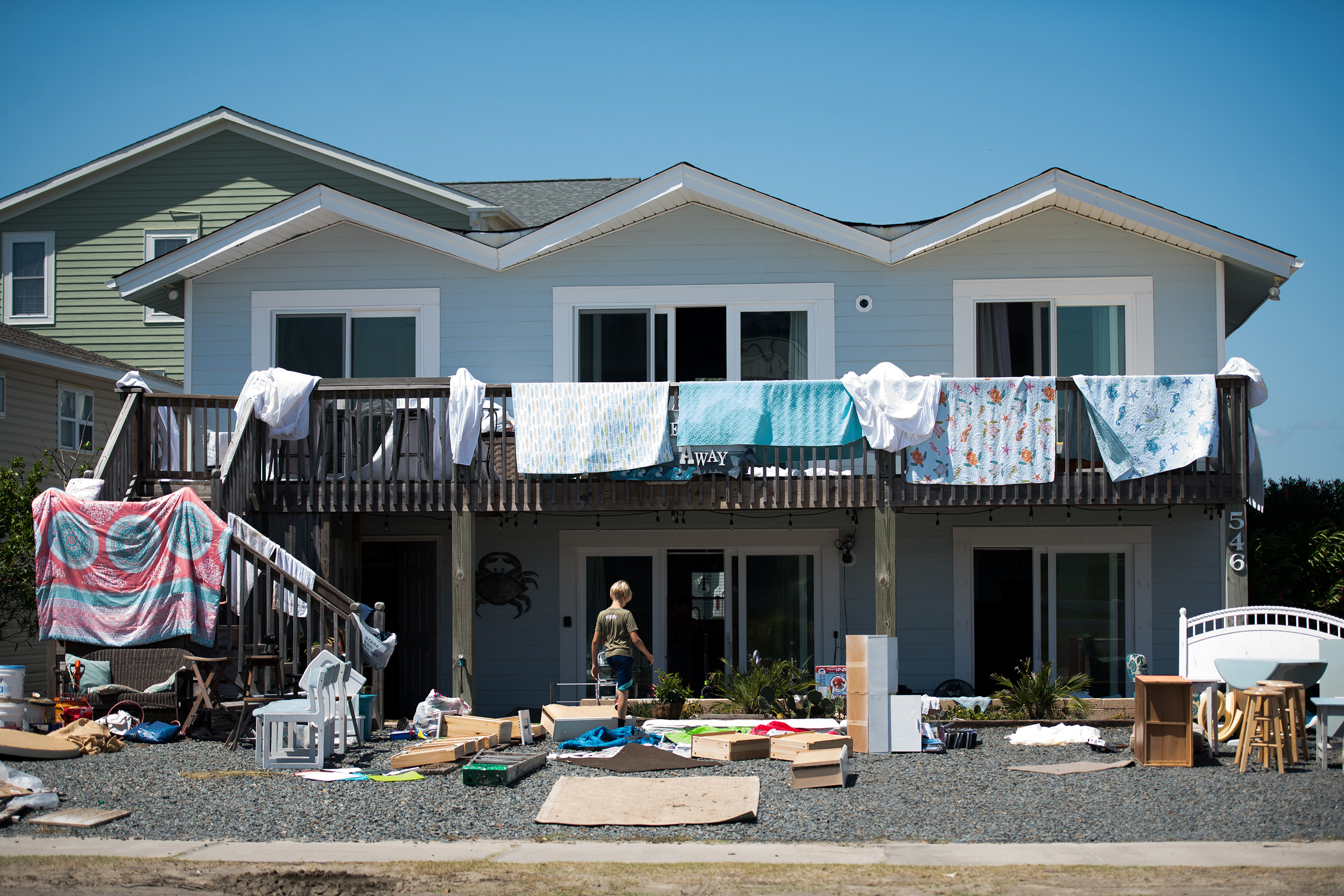 Bedsheets are draped over a second-story railing of a house surrounded by furniture moved outside to dry