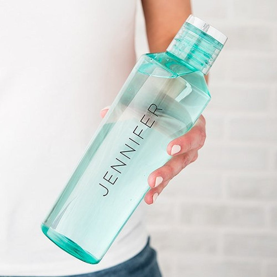 "Customizable water bottle from Love and Luxe Handmade on Etsy with custom text reading ""Jennifer"" printed vertically on the bottle"