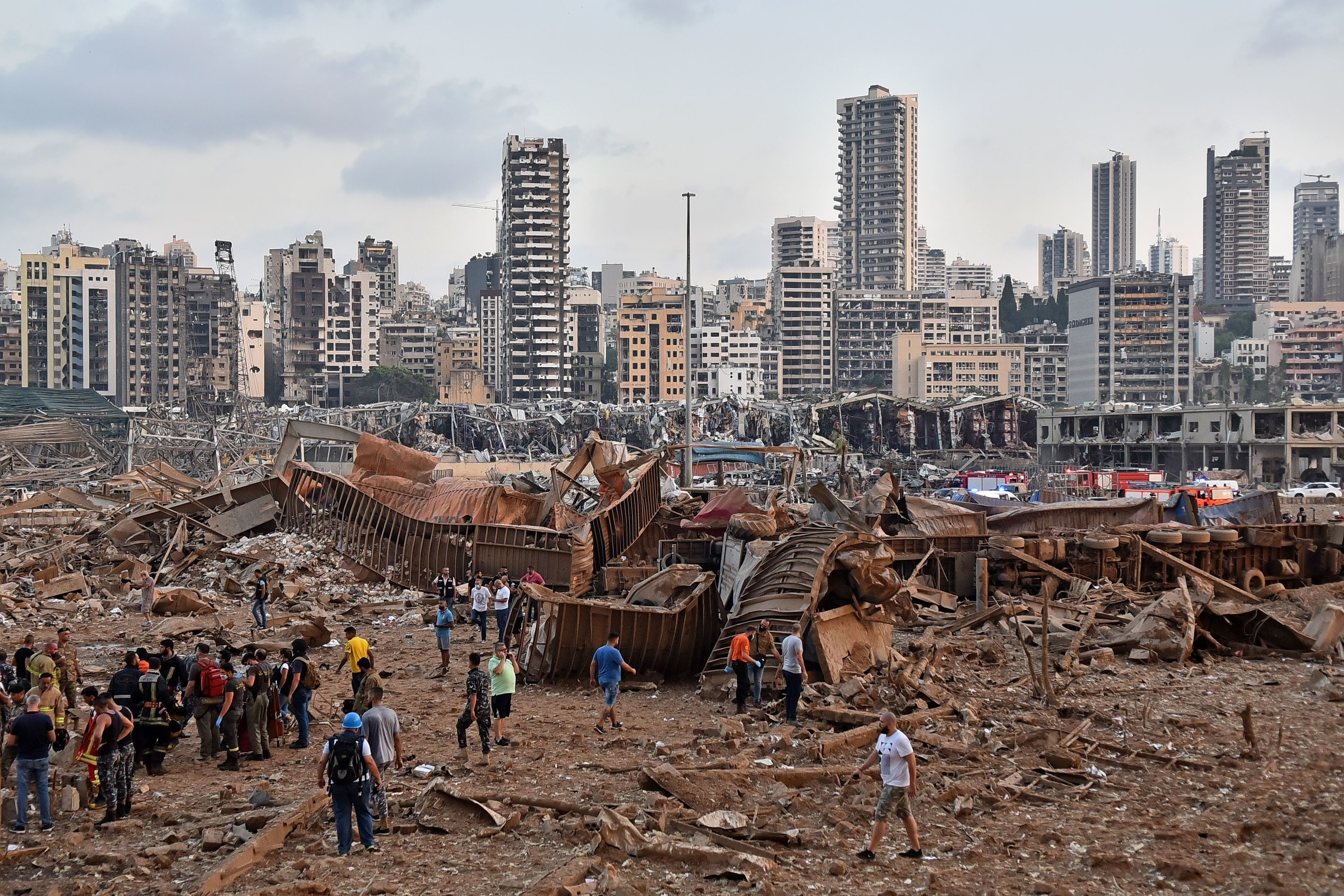 People walk around debris and twisted metal with heavily damaged high-rises in the background