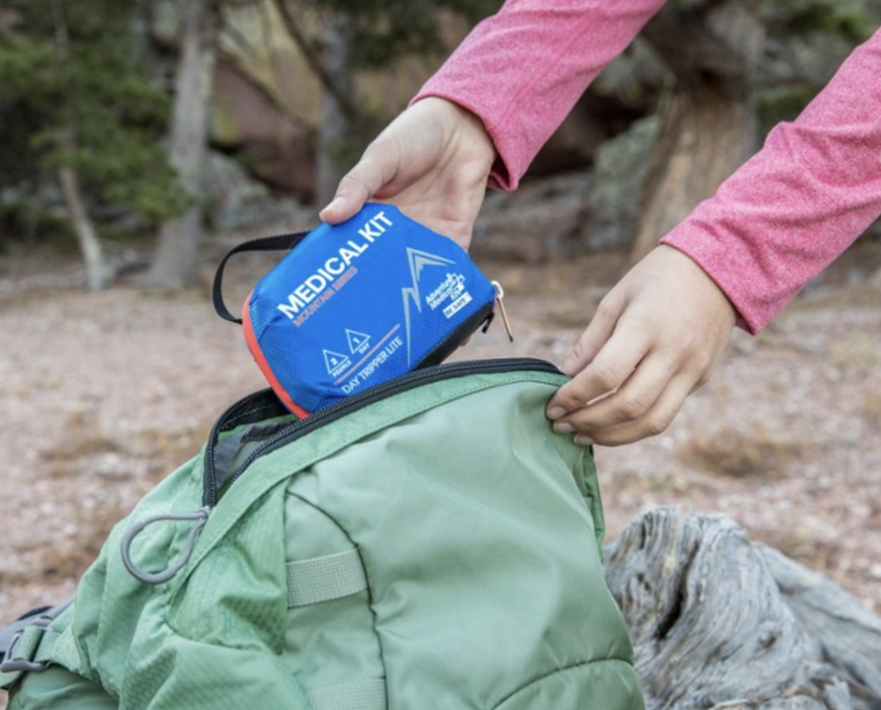 hands reaching for a small blue medical kit in a backpack