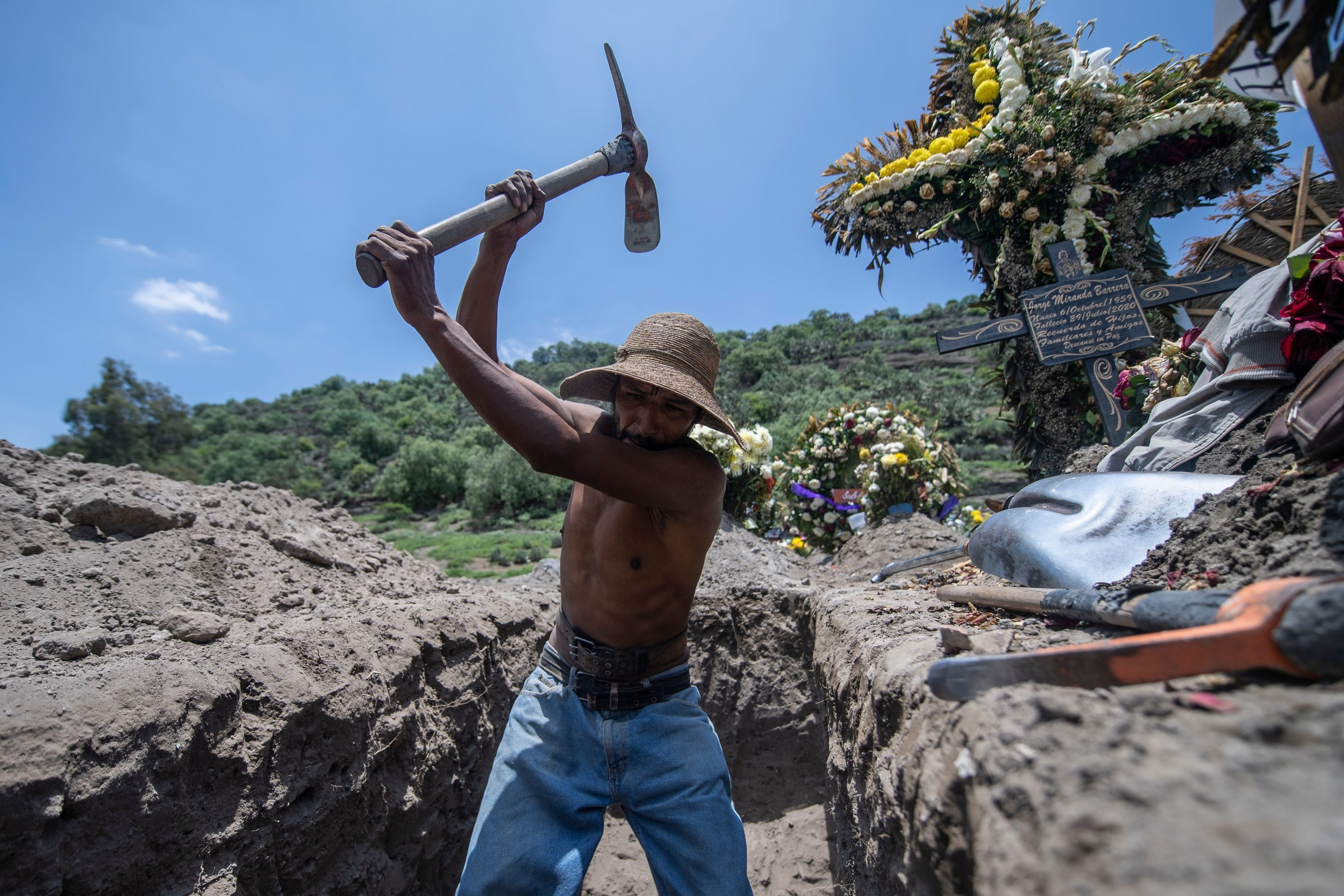 A shirtless man wearing jeans and a sombrero swings a pickax in a grave surrounded by wreaths of flowers