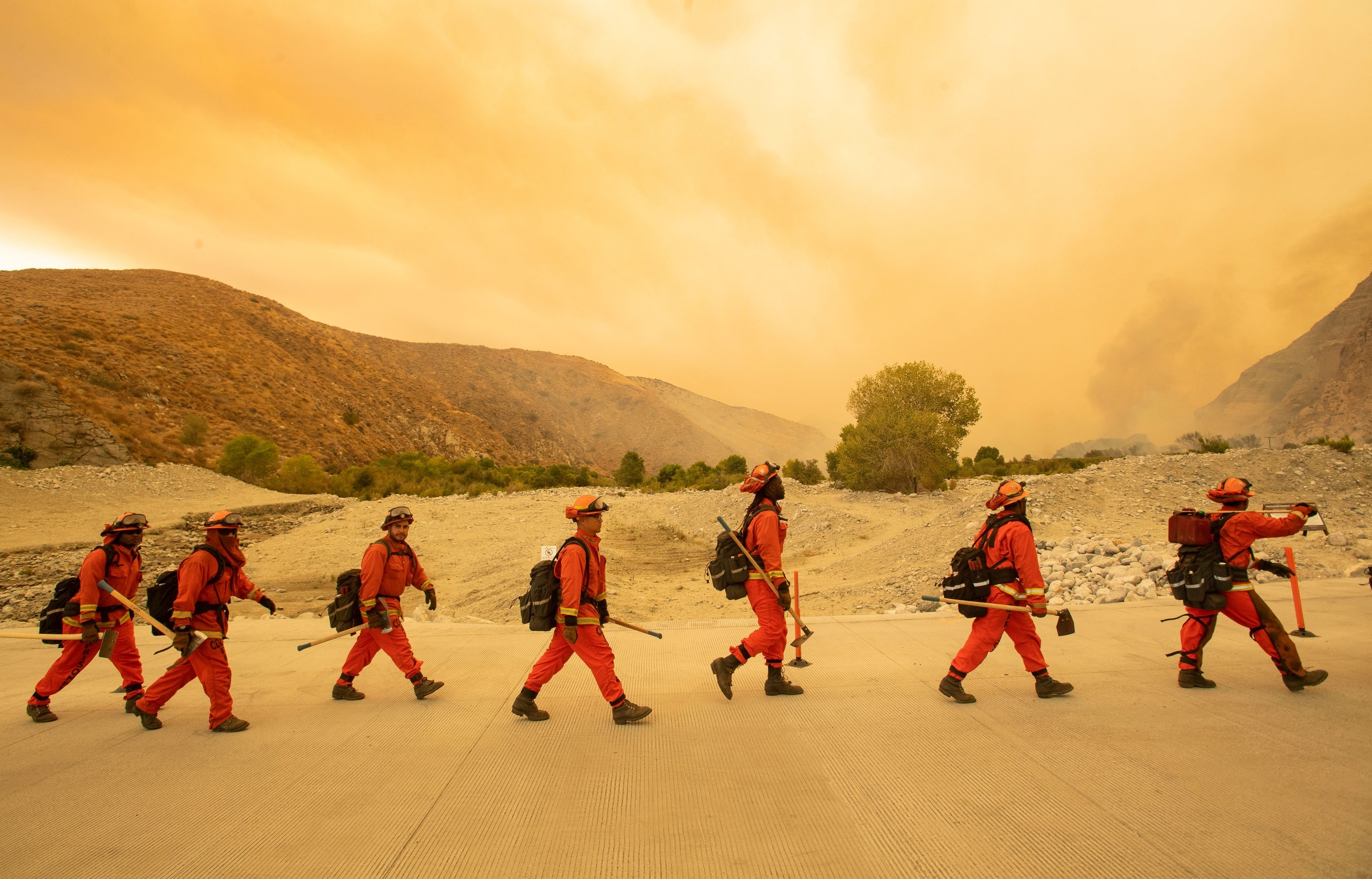 Men in orange firefighting suits walk in a line carrying axes  along a rocky ridge with a yellow-orange sky caused by smoke