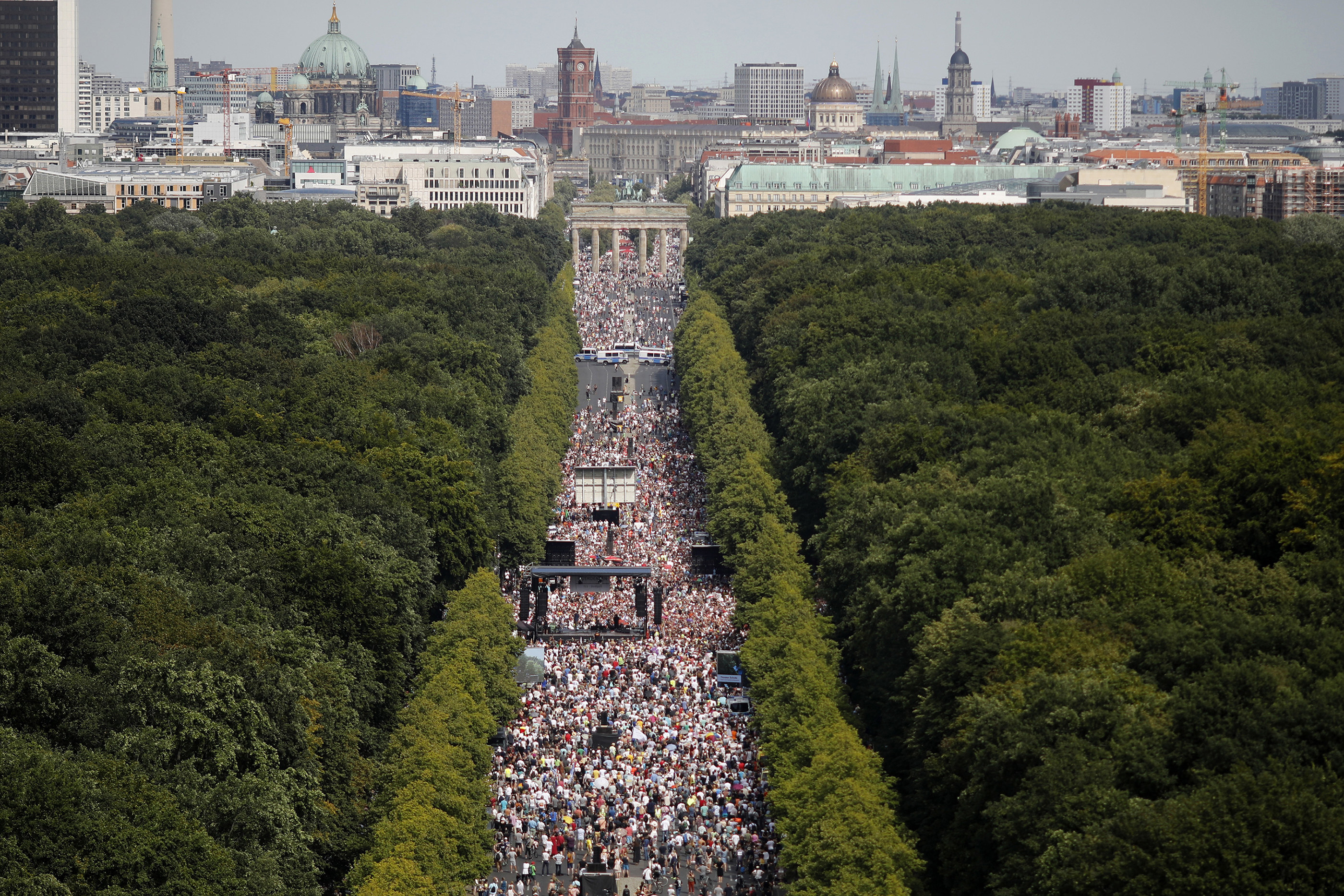 An aerial shot of thousands of people walking down a boulevard surrounded by trees and toward the skyline of Berlin