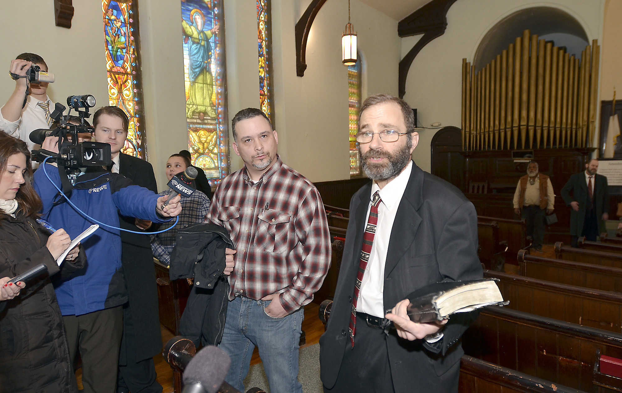 A camera crew interviews two men in a church. One holds a bible