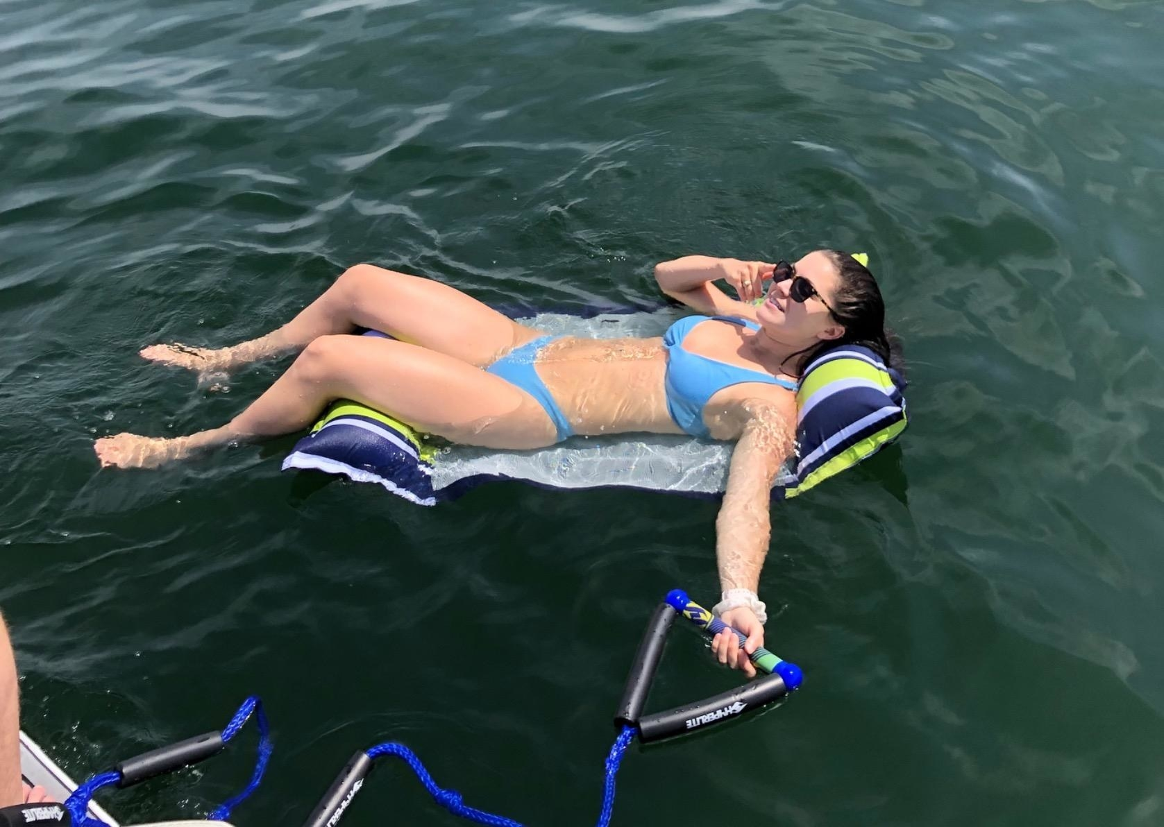 Reviewer relaxing on the float, which has a pillow for the neck and the legs