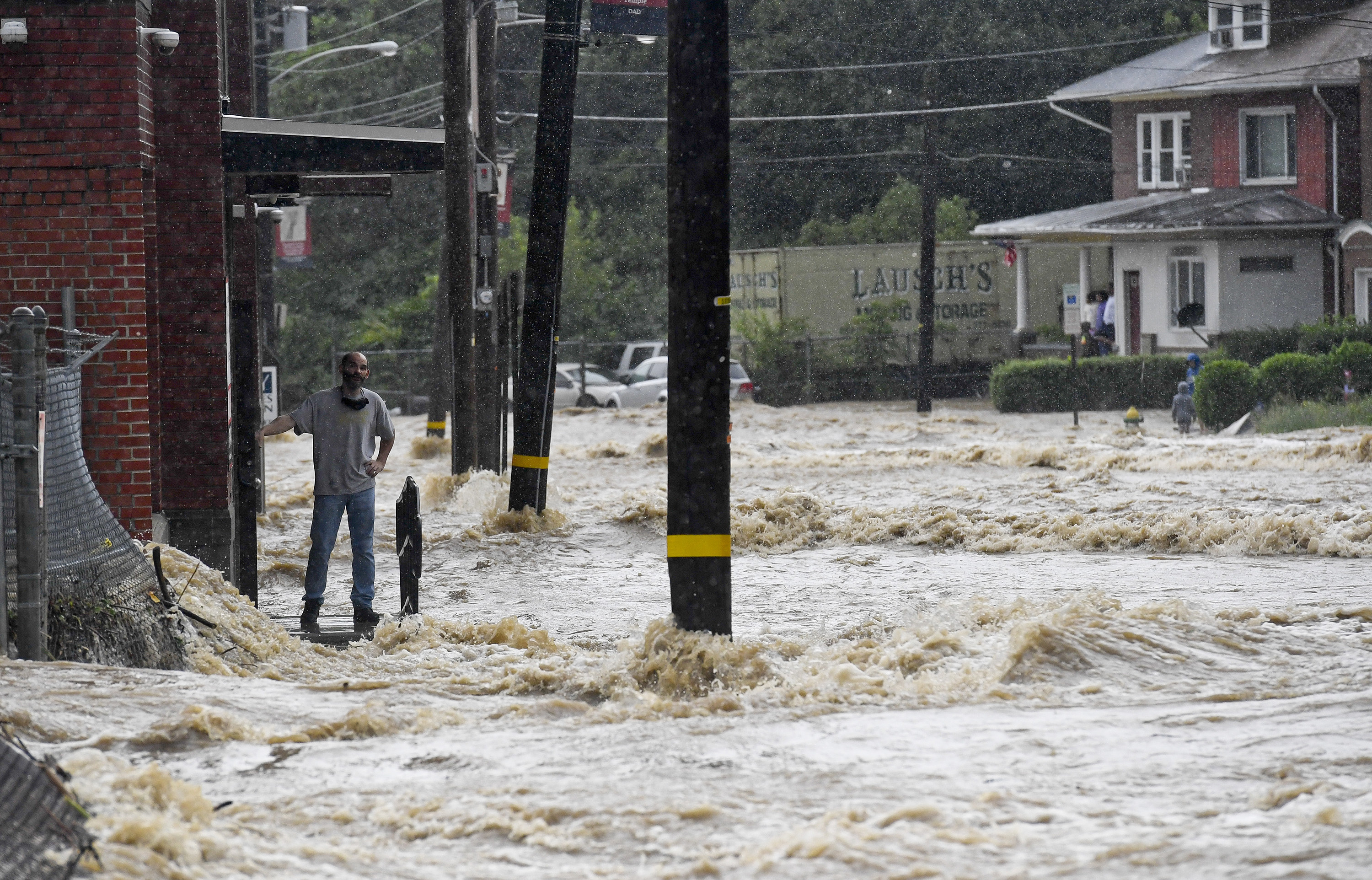 A man stands watching choppy muddy water come down the street