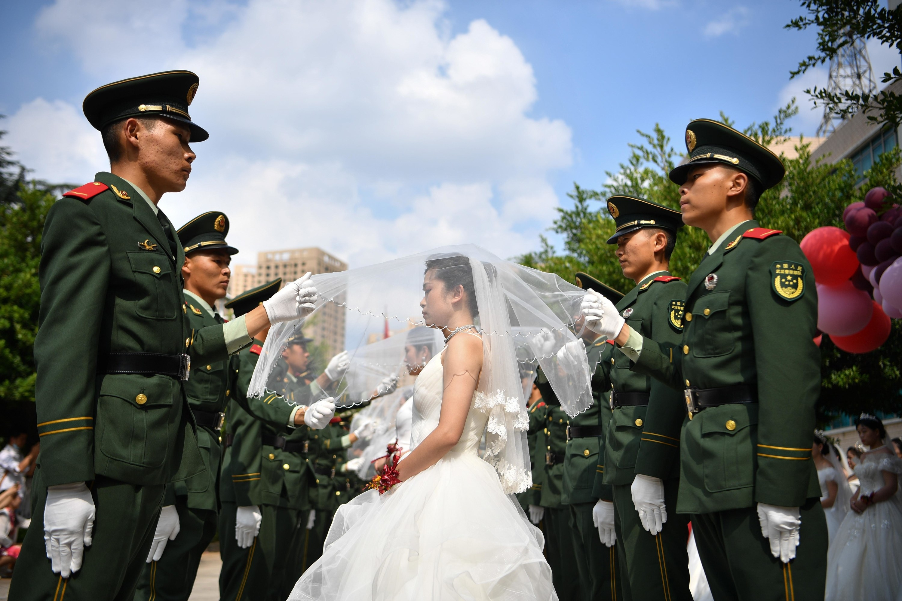 Two lines of soldiers in green formal uniforms, with a line of brides in white standing in between them