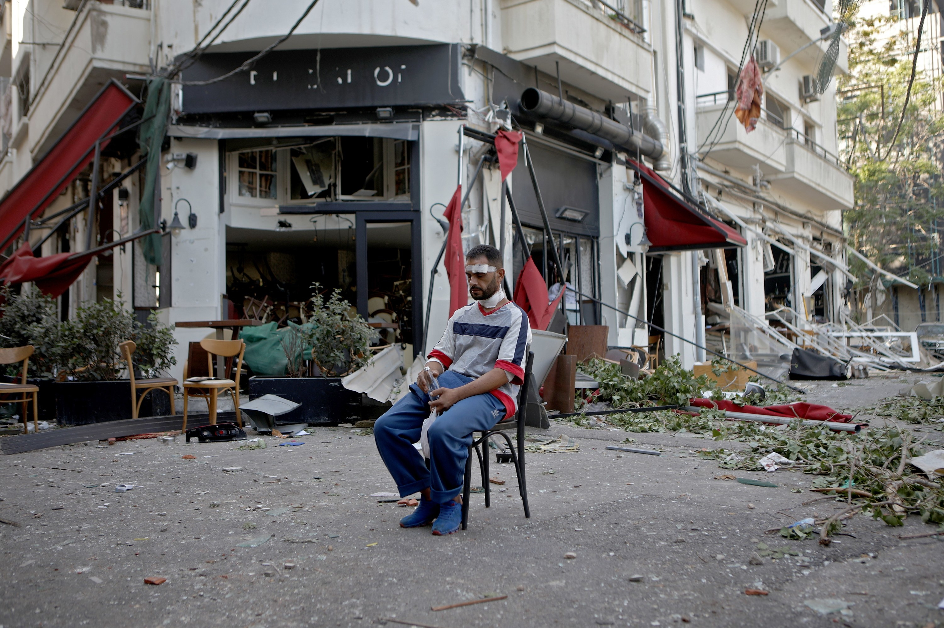 A man with a bandaged head and neck sits on a dining chair, alone on an empty street filled with rubble