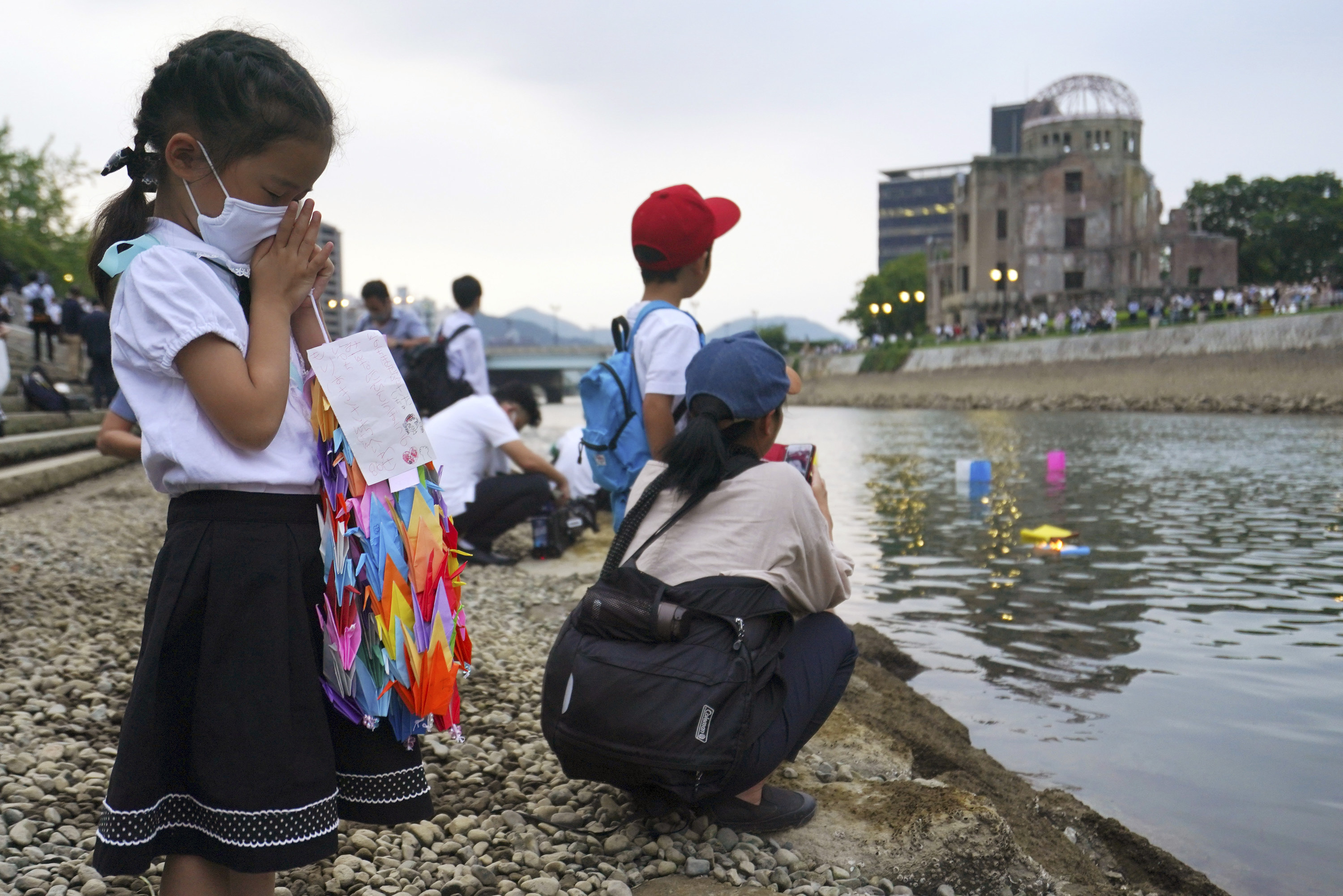 A small girl with her hands folded in front of her face holds colorful paper cranes standing along the waterline of a river where other children are gathered
