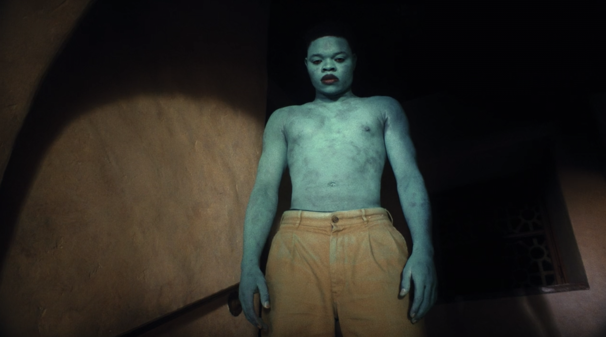 "Papi Ojo stands on a staircase the blue man in ""Black Is King"""