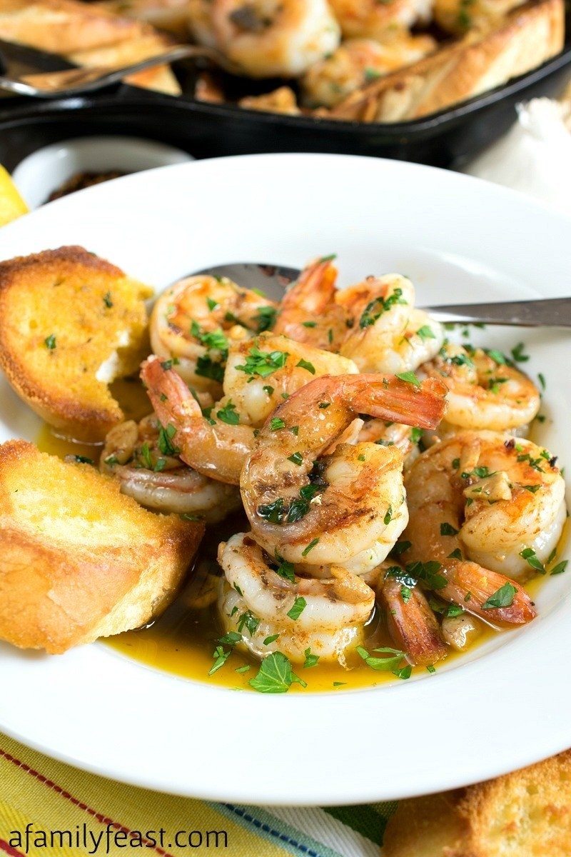 A bowl filled with a light broth, crispy sliced bread, and a pile of succulent, glistening shrimp topped with fresh herbs