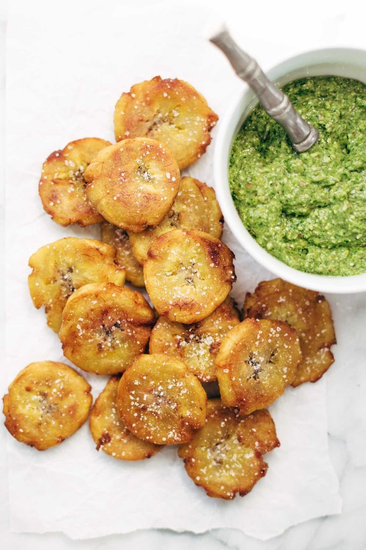 A pile of crispy, fried plantain slices topped with a healthy sprinkle of salt and a side of an herby, creamy dipping sauce