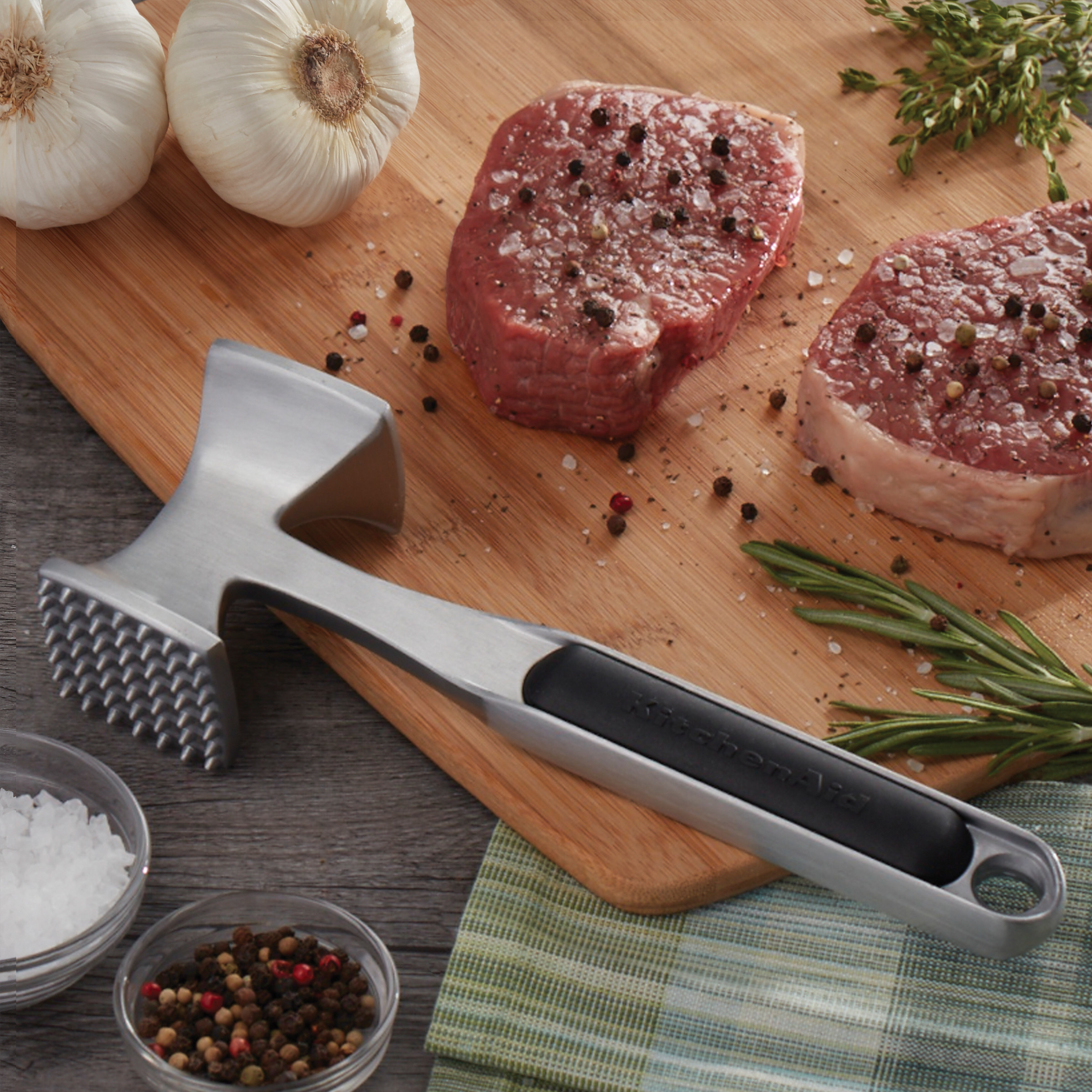 KitchenAid meat tenderizer laying on a cutting board next to peppered steaks