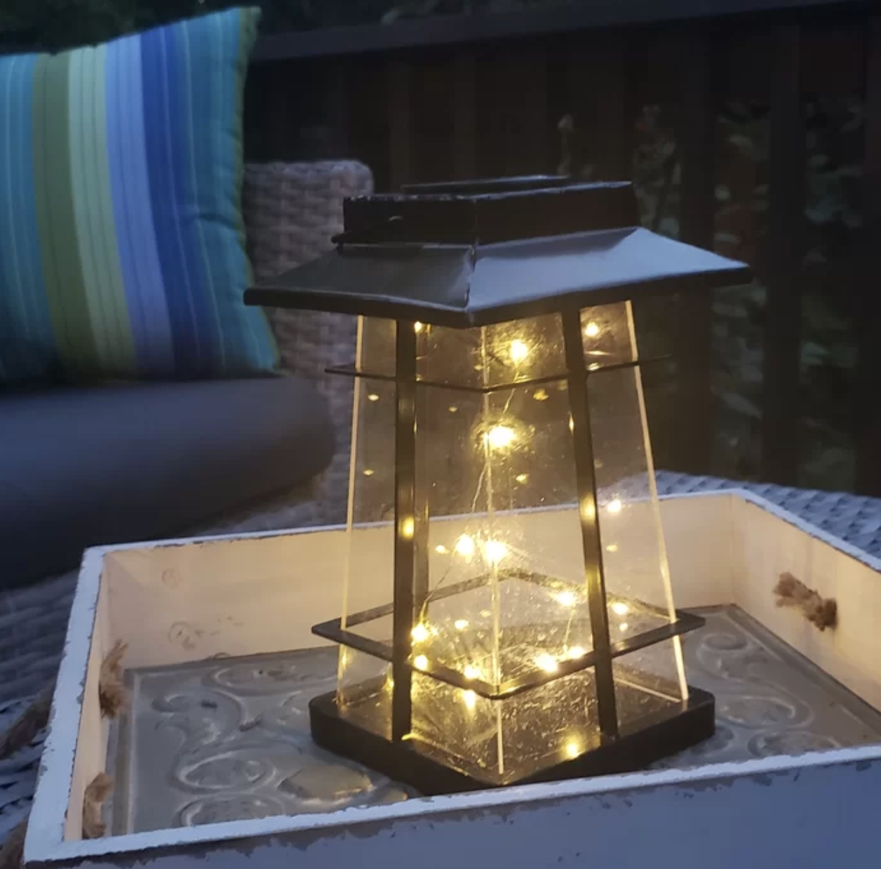 The lantern is iron and clear plastic and has fairy lights inside