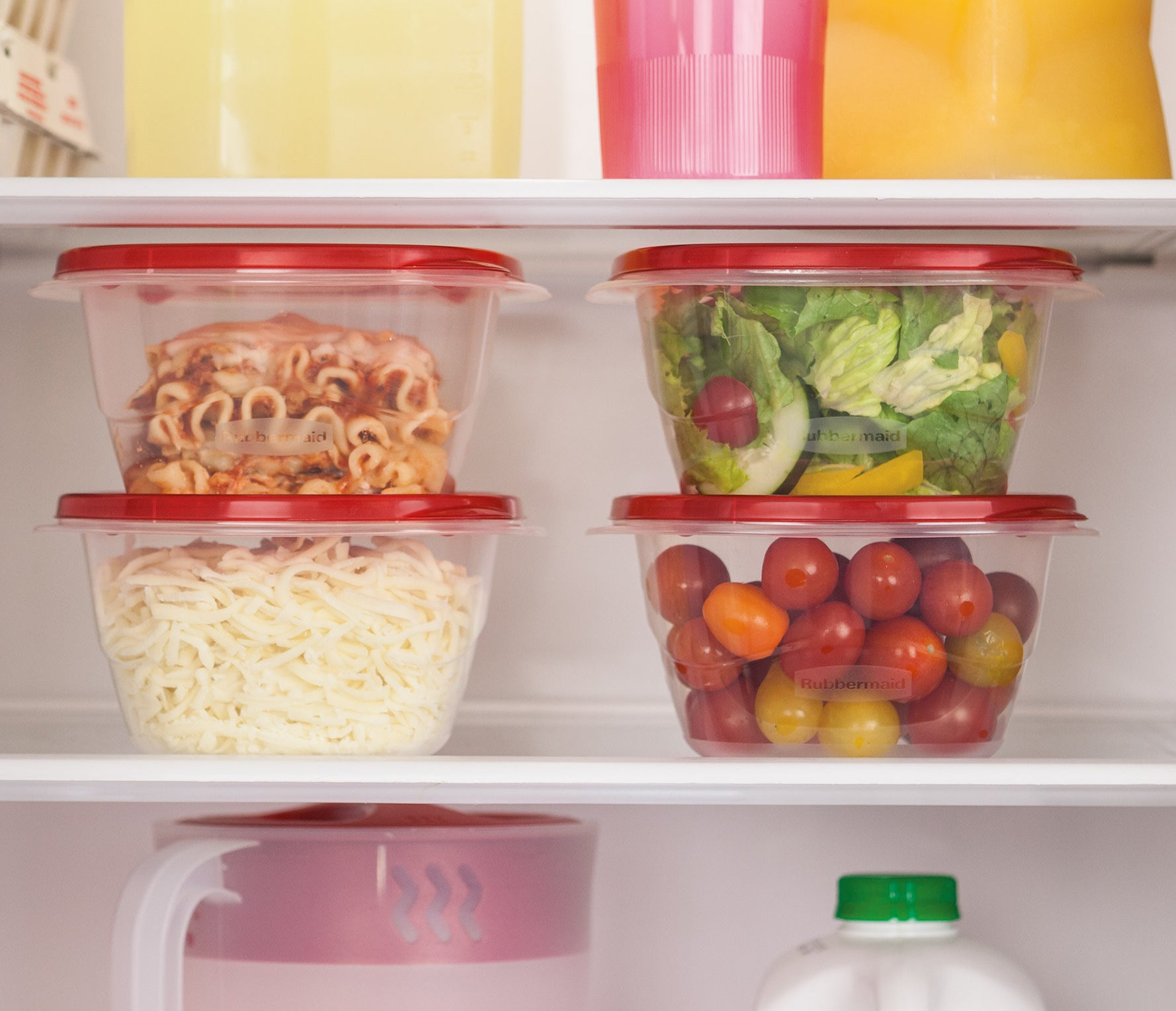 four food containers with red lids holding various leftovers in a fridge