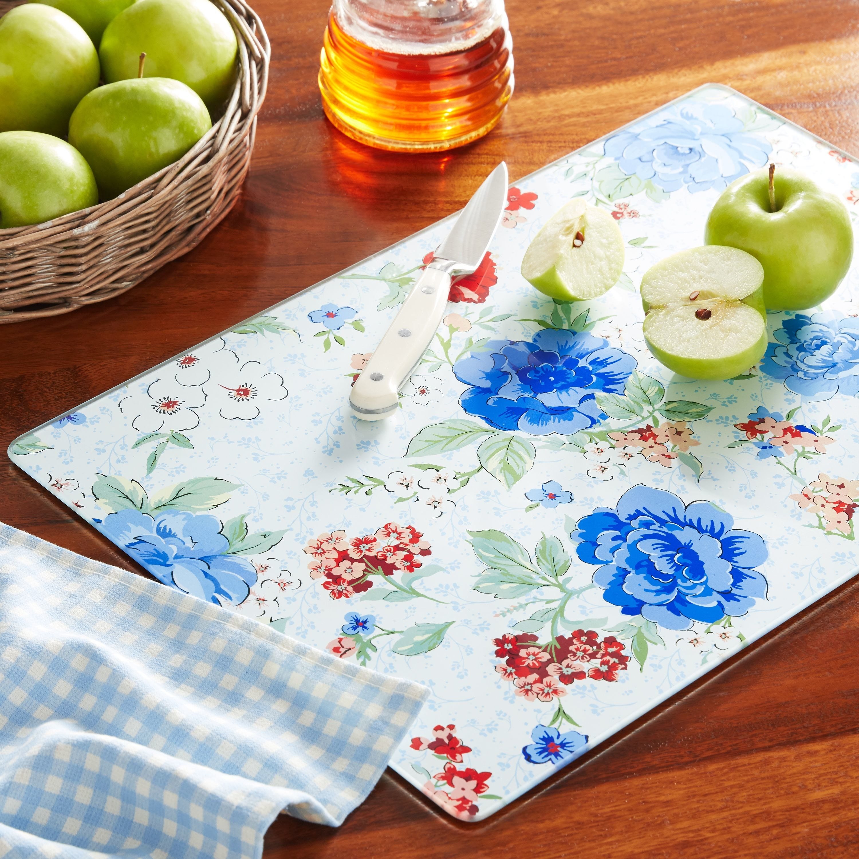Floral-printed glass cutting board with apples on it