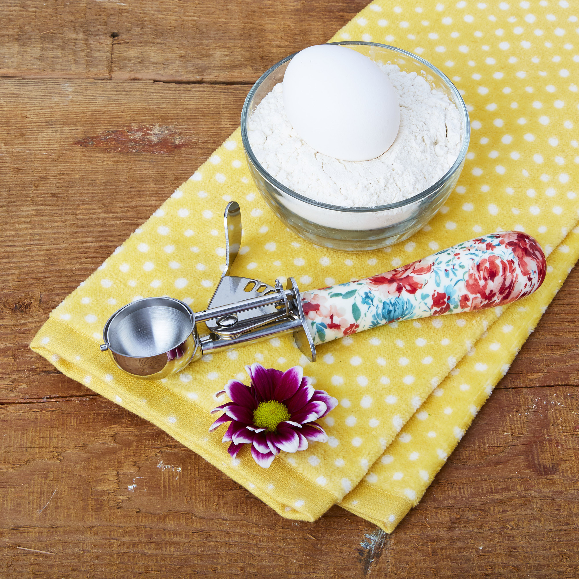 A silver and floral cookie scoop laying on a yellow hand towel