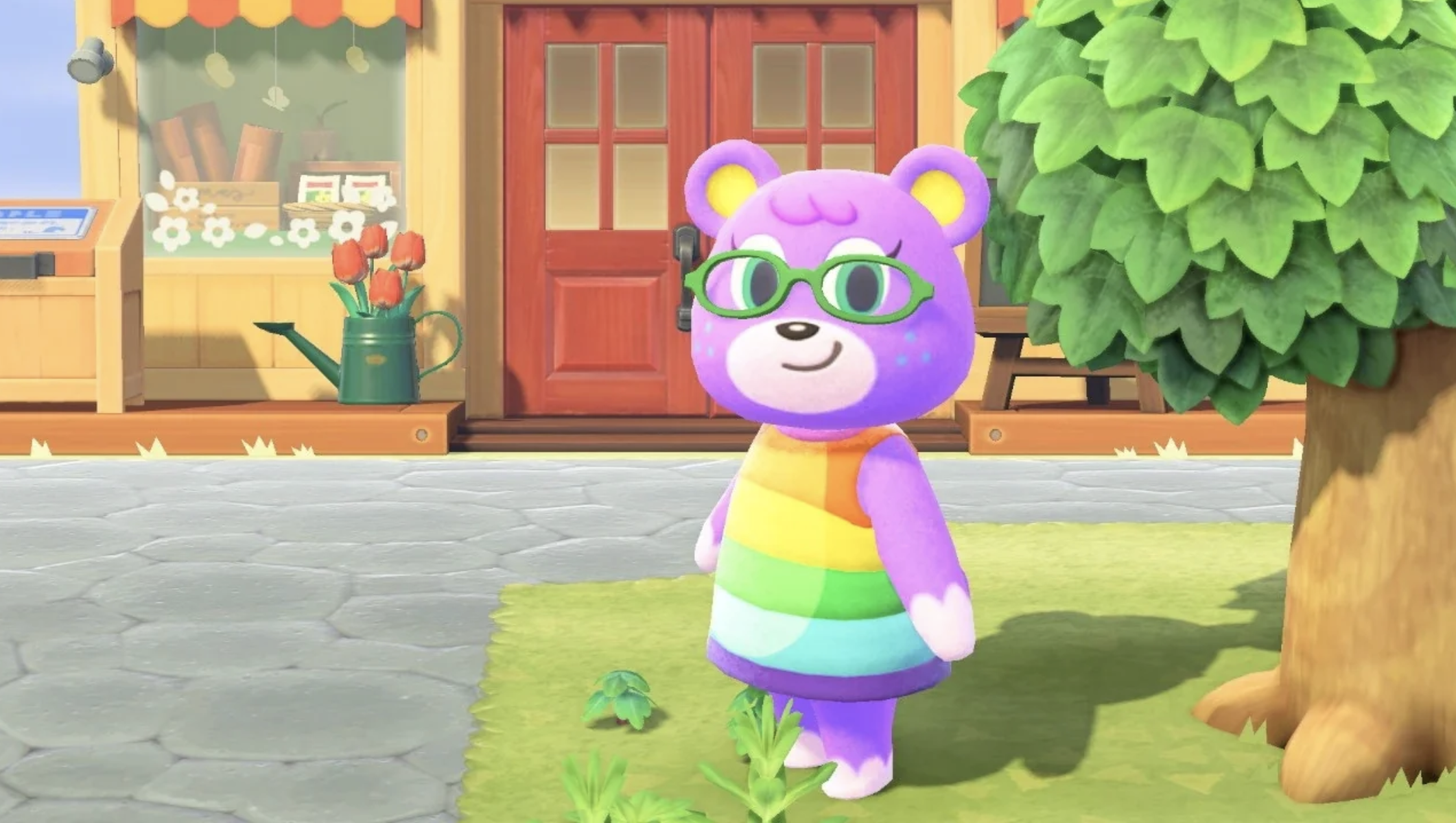 Megan wears a cute pair of rounded glasses and smiles in front of Nook's Cranny