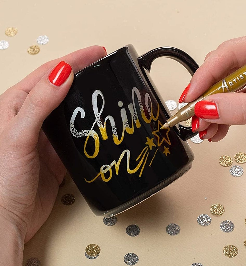 A person writing on a mug with a metallic paint pen