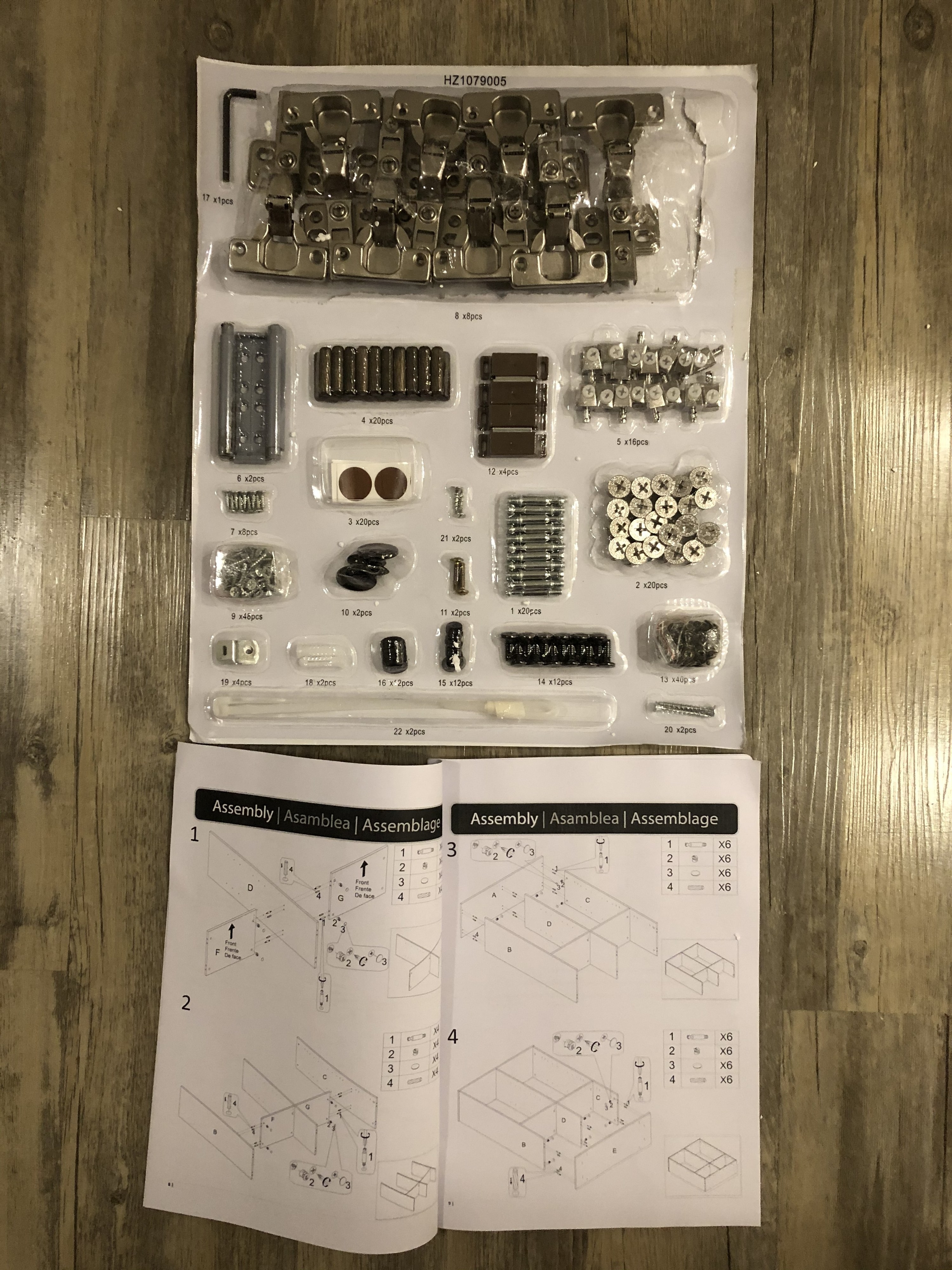 A package of dozens of different types of screws, nails, and hinges, with a complicated instruction manual for assembling the china cabinet.