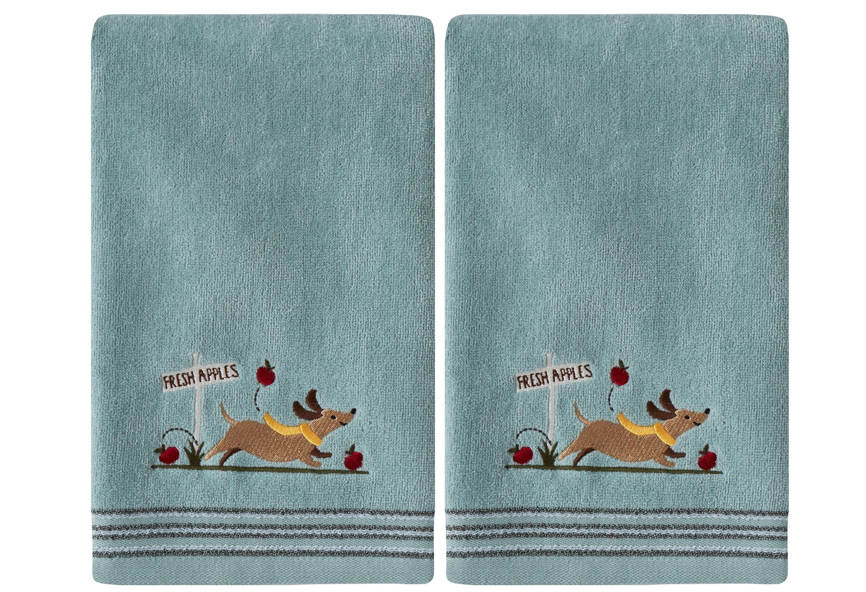 "The two blue hand towels with a picture of a dog running with apples and a sign that says ""fresh apples"""