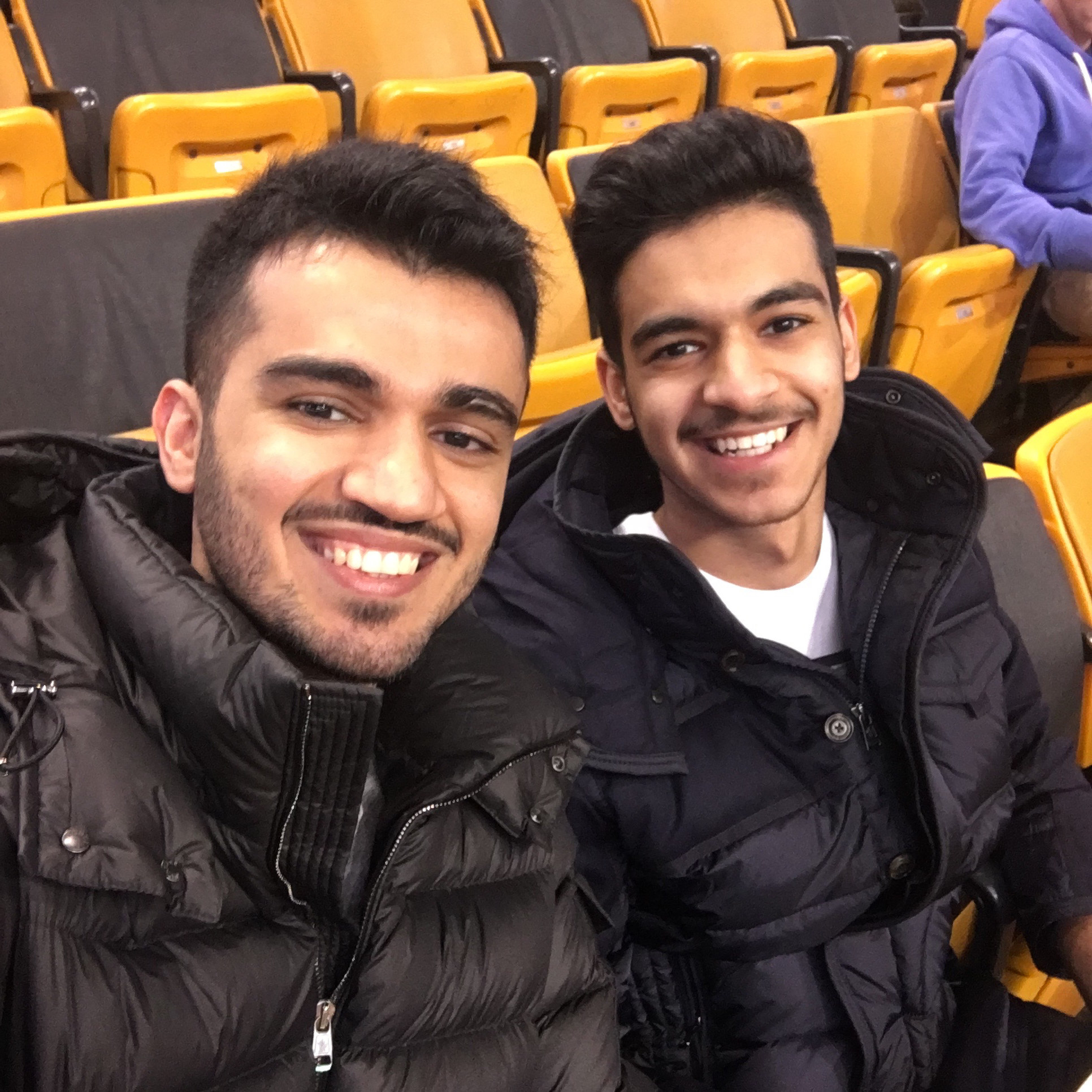 Khalid and Omar Aljabri smile while sitting in a stadium