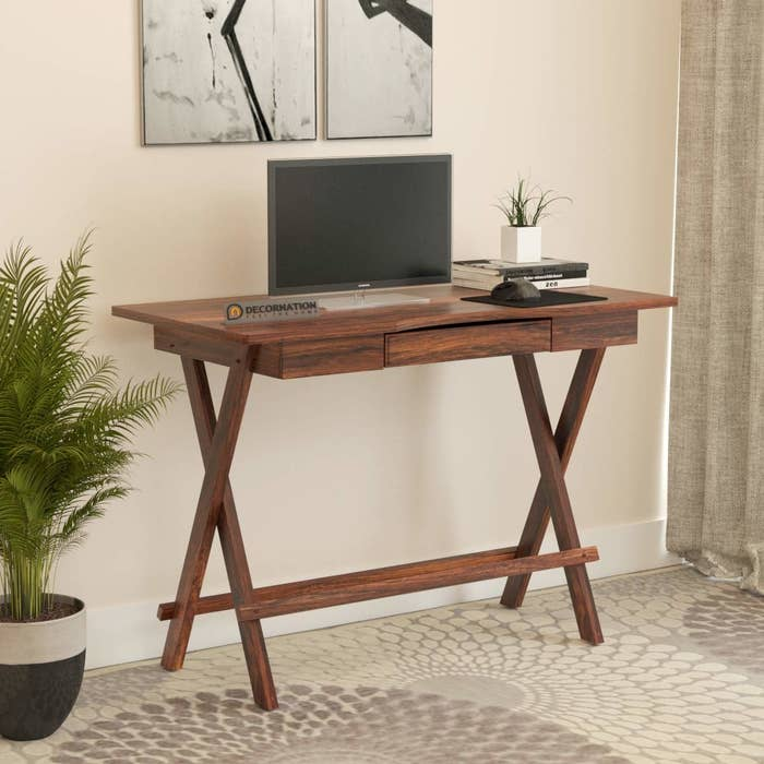A wooden table with a monitor and some stationery on it, placed next to a tall plant