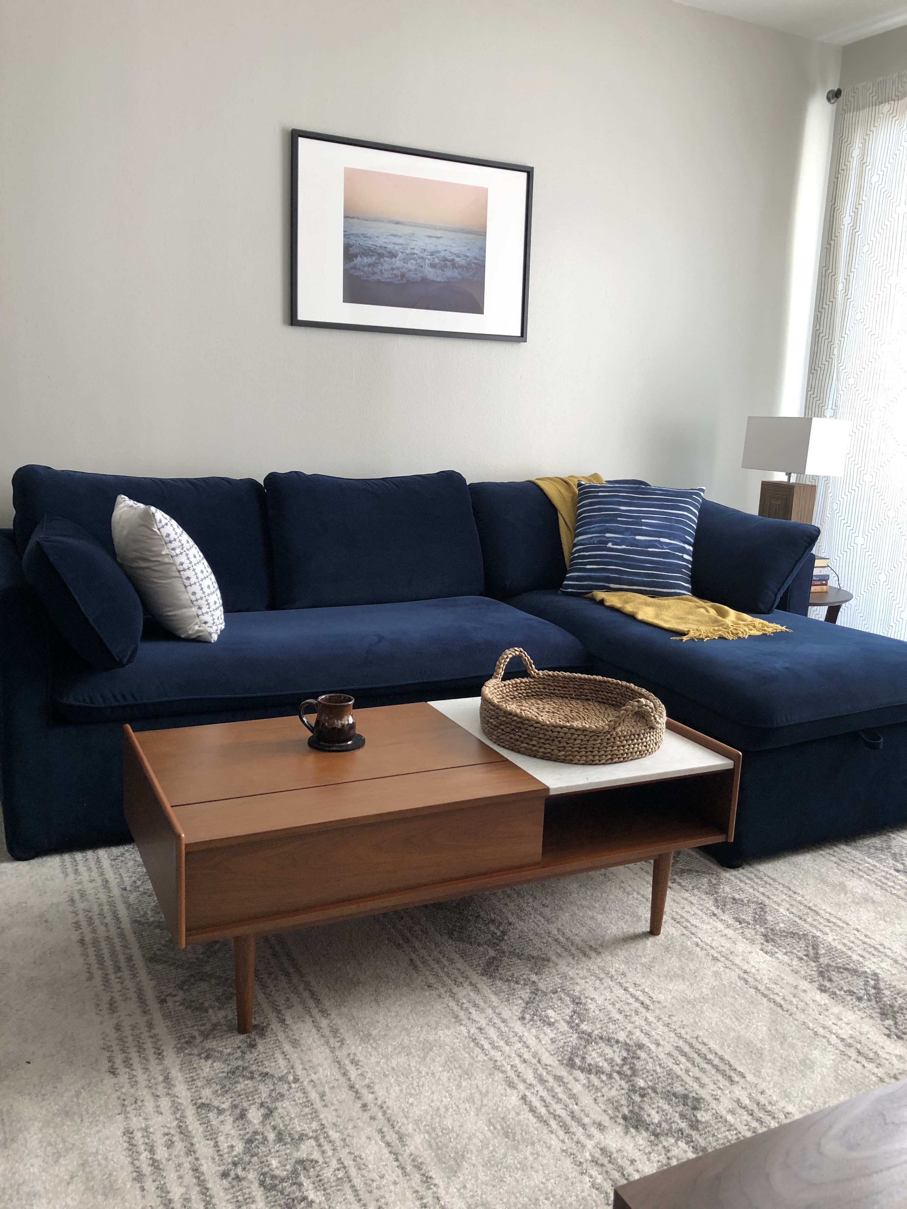 Photo of completed navy blue couch, with artwork up, rug in place, and coffee table.