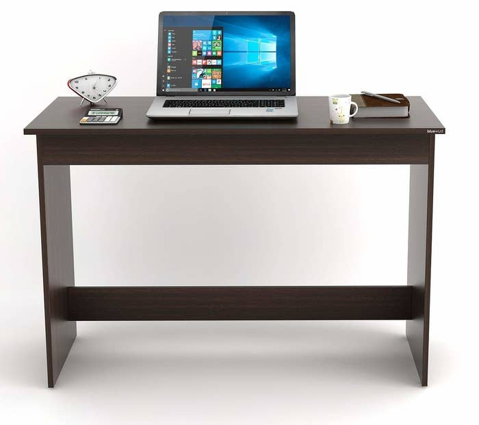A wooden desk with a laptop, mug, and some stationery on it