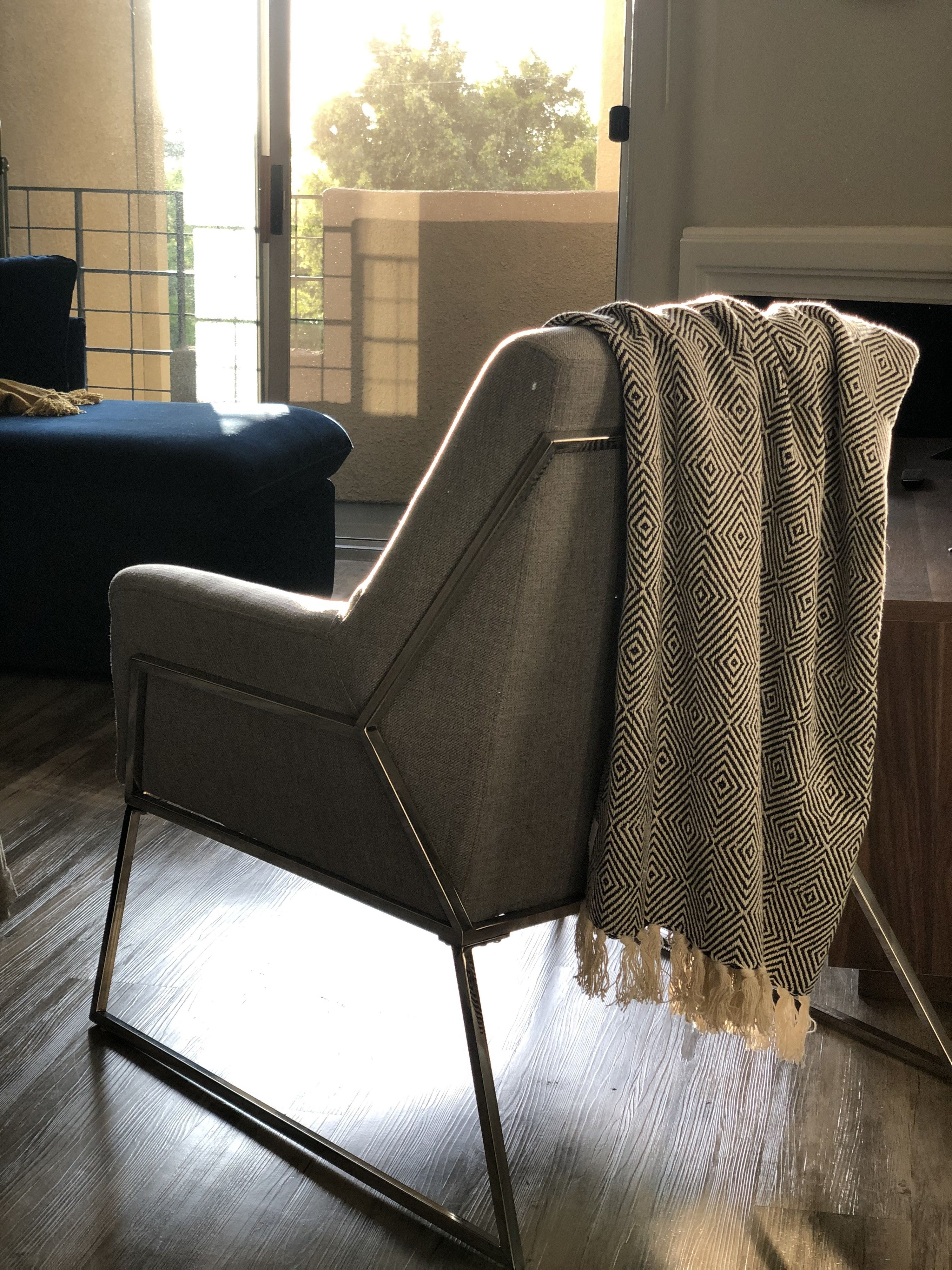 Portrait mode photo of mid-century modern gray armchair with a gray patterned throw blanket.