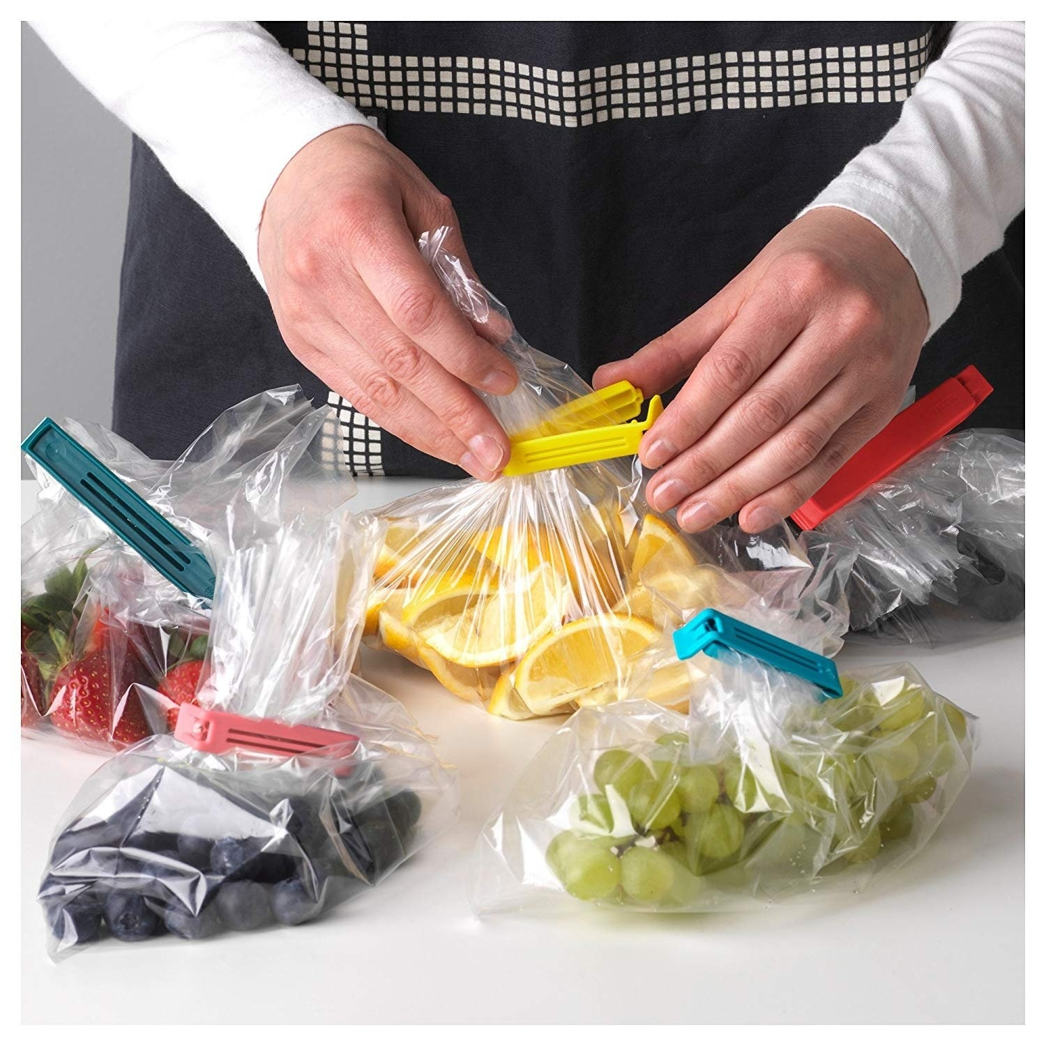 A person's hand using baggie seals to seal plastic bags with food in them.