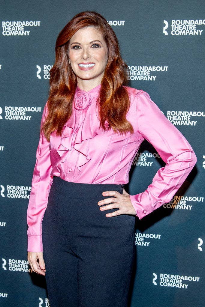 Debra Messing posing with her hand on her hip on a March 2020 red carpet