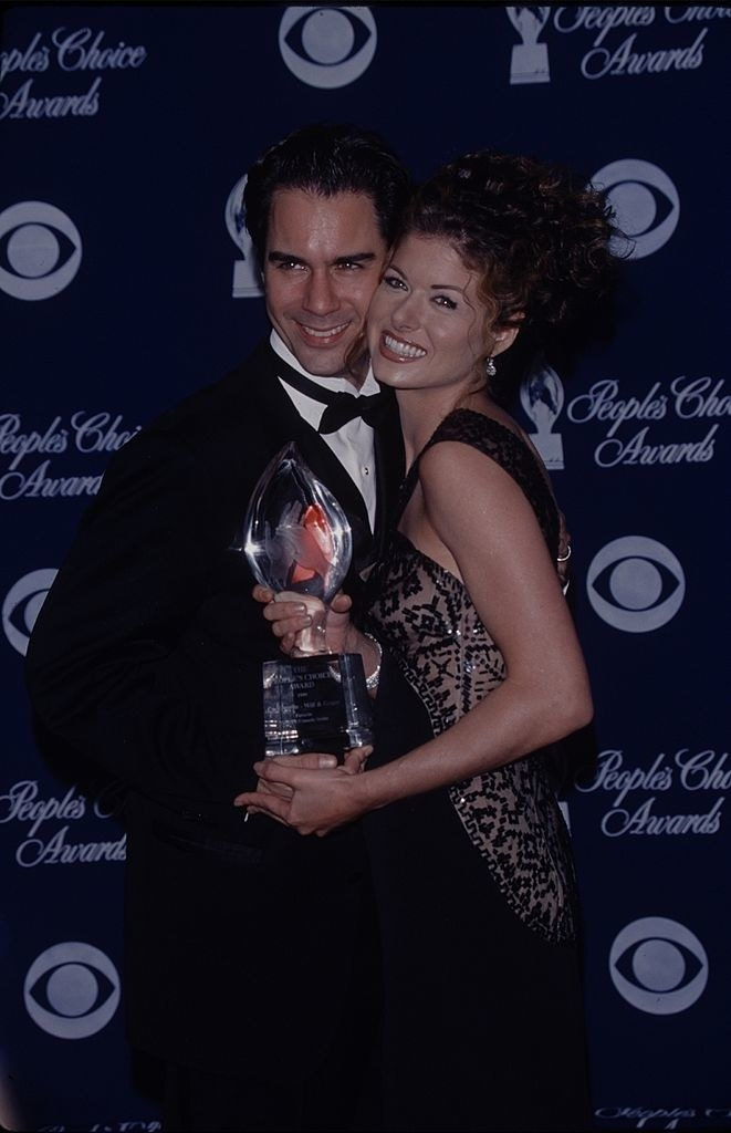 Debra Messing and Eric McCormack holding award on a red carpet together smiling
