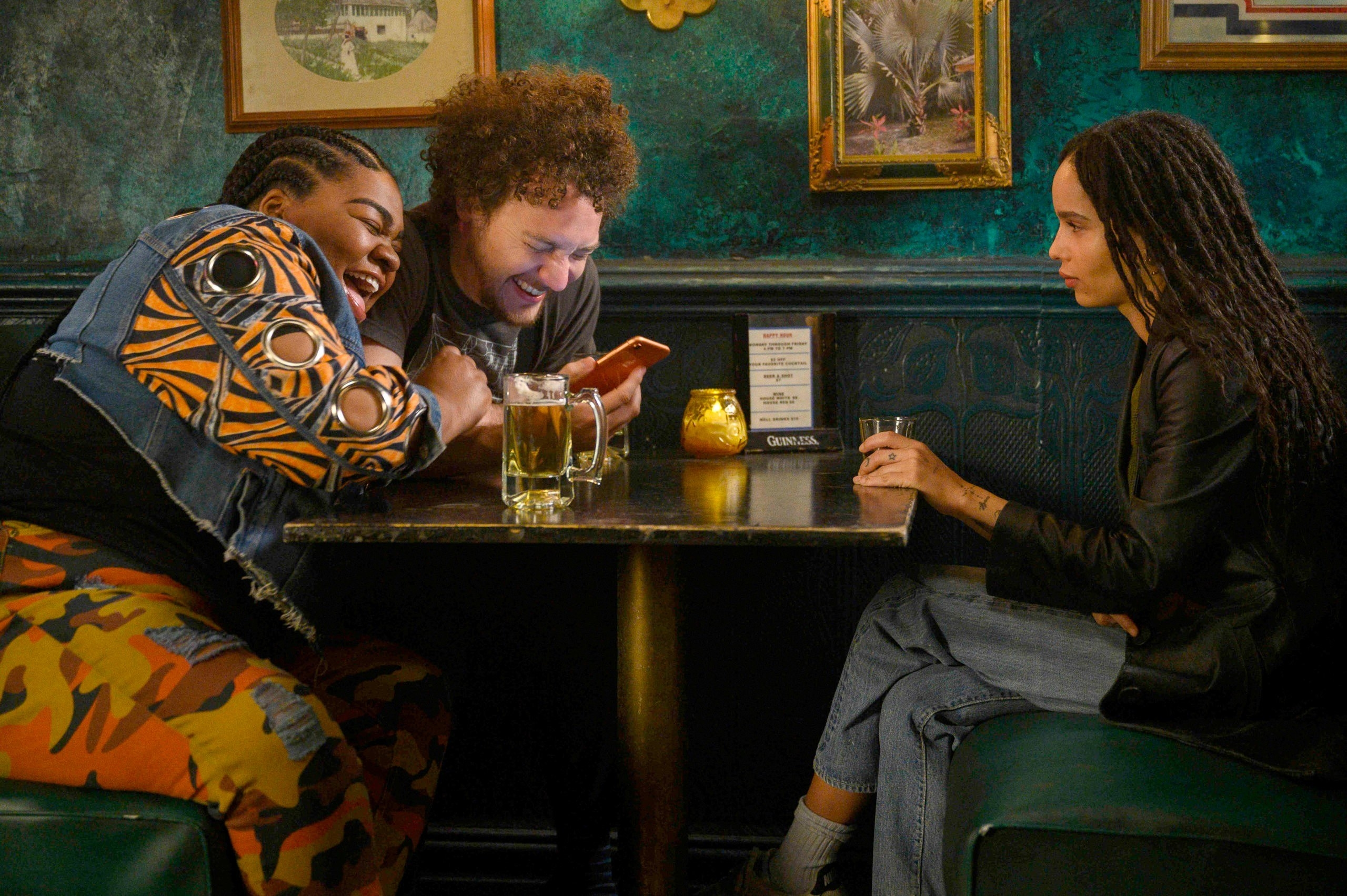 """Friends laughing at something on a phone in a bar booth in """"High Fidelity"""" scene"""