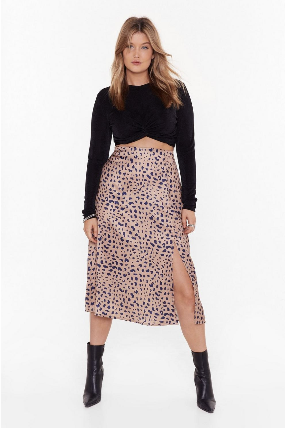 A model wearing a long sleeved-black crop top and a high-waisted pink midi skirt that has one leg slit.