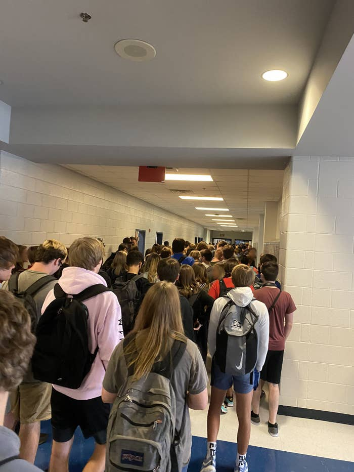 Students wait in a crowded school hallway